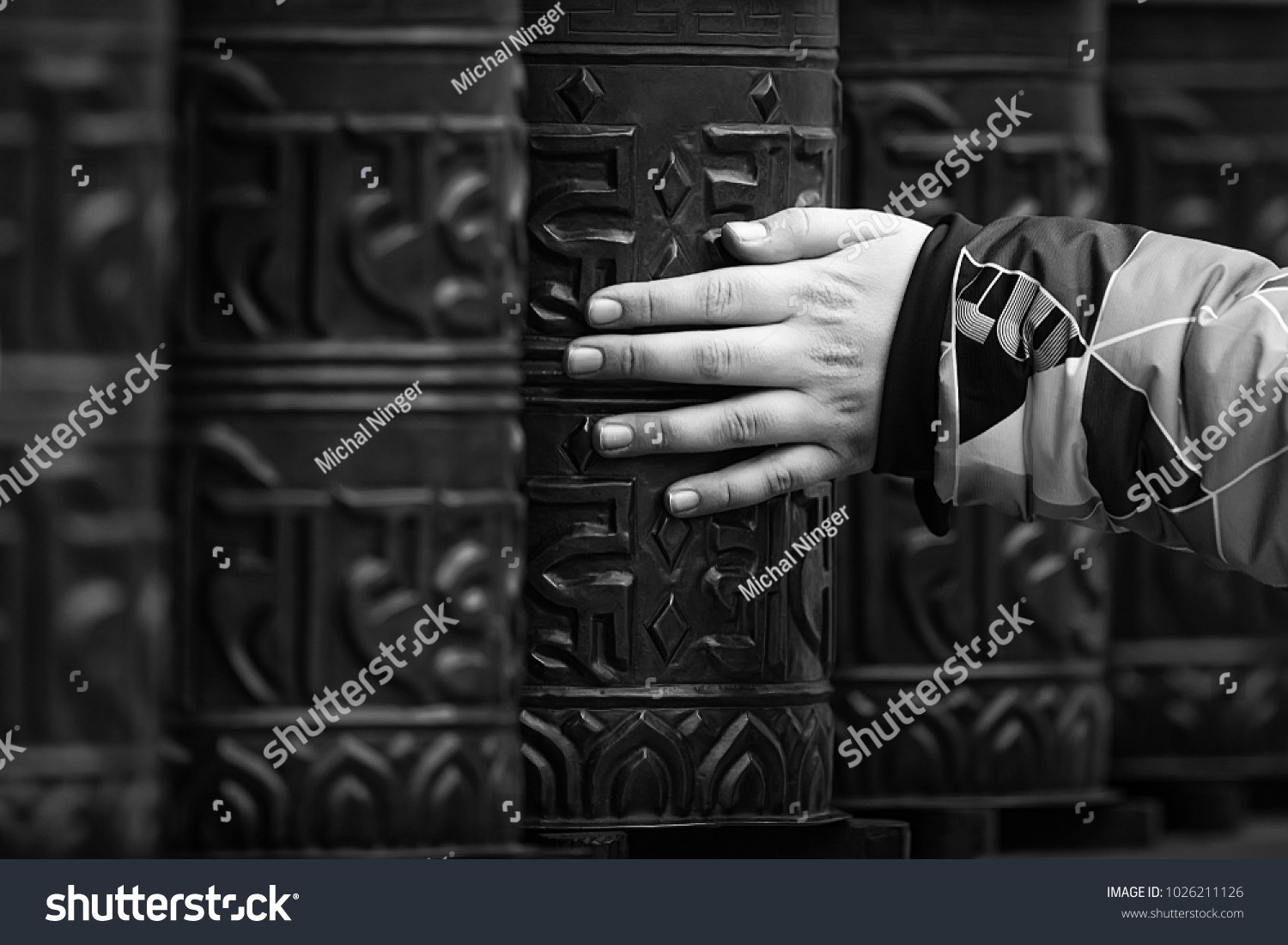 hand is rotaitng prayer wheels in the buddhism tample, black and white