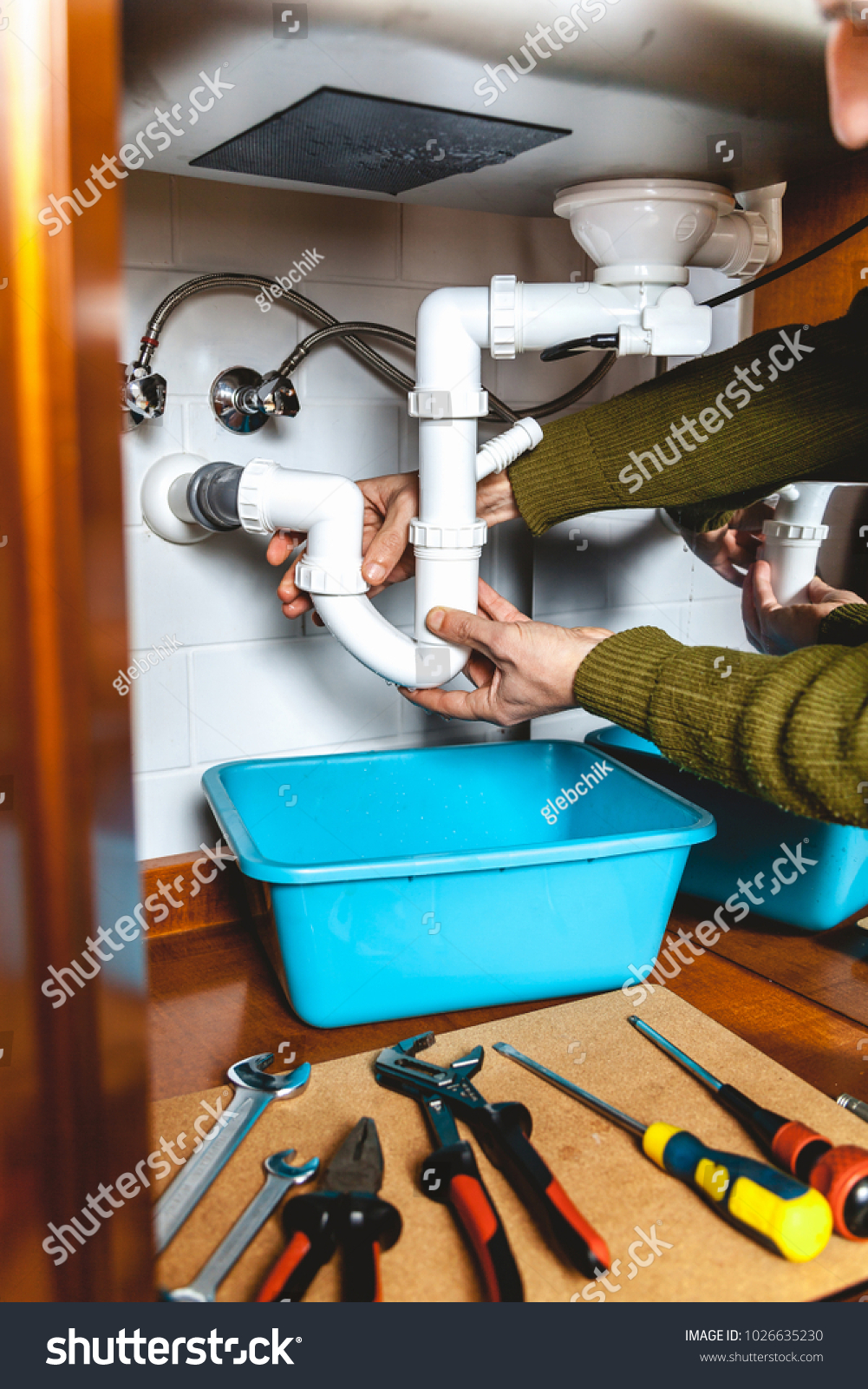 Hands apart the plumbing connections of plastic pipe kitchen ...
