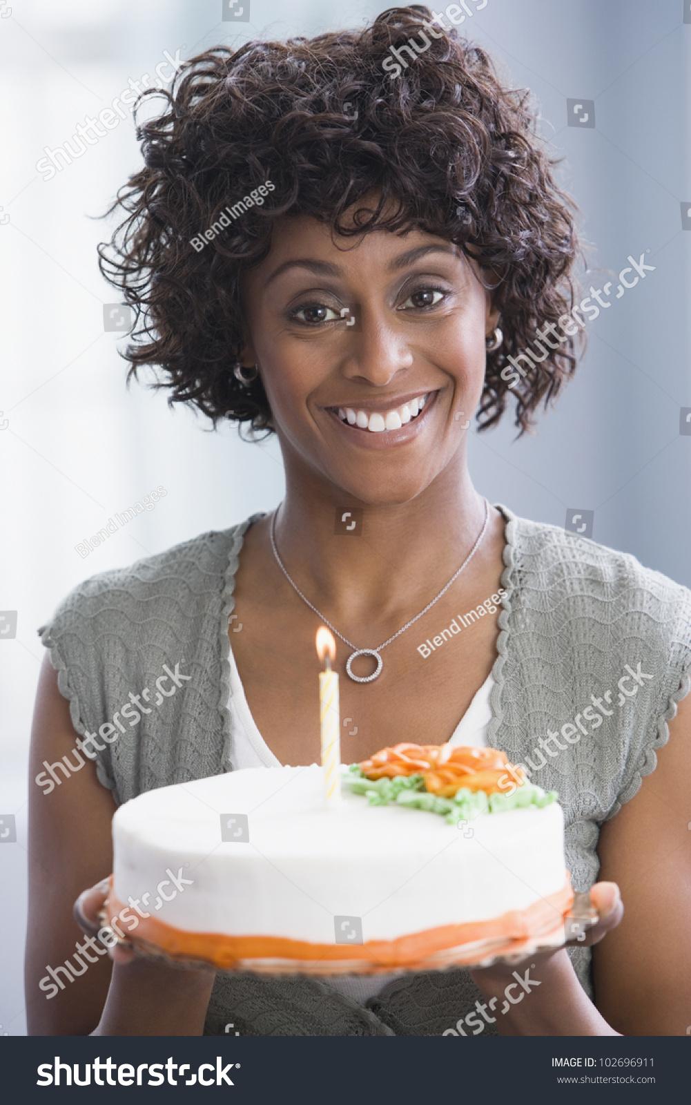 African American Woman Holding Birthday Cake Stock Photo