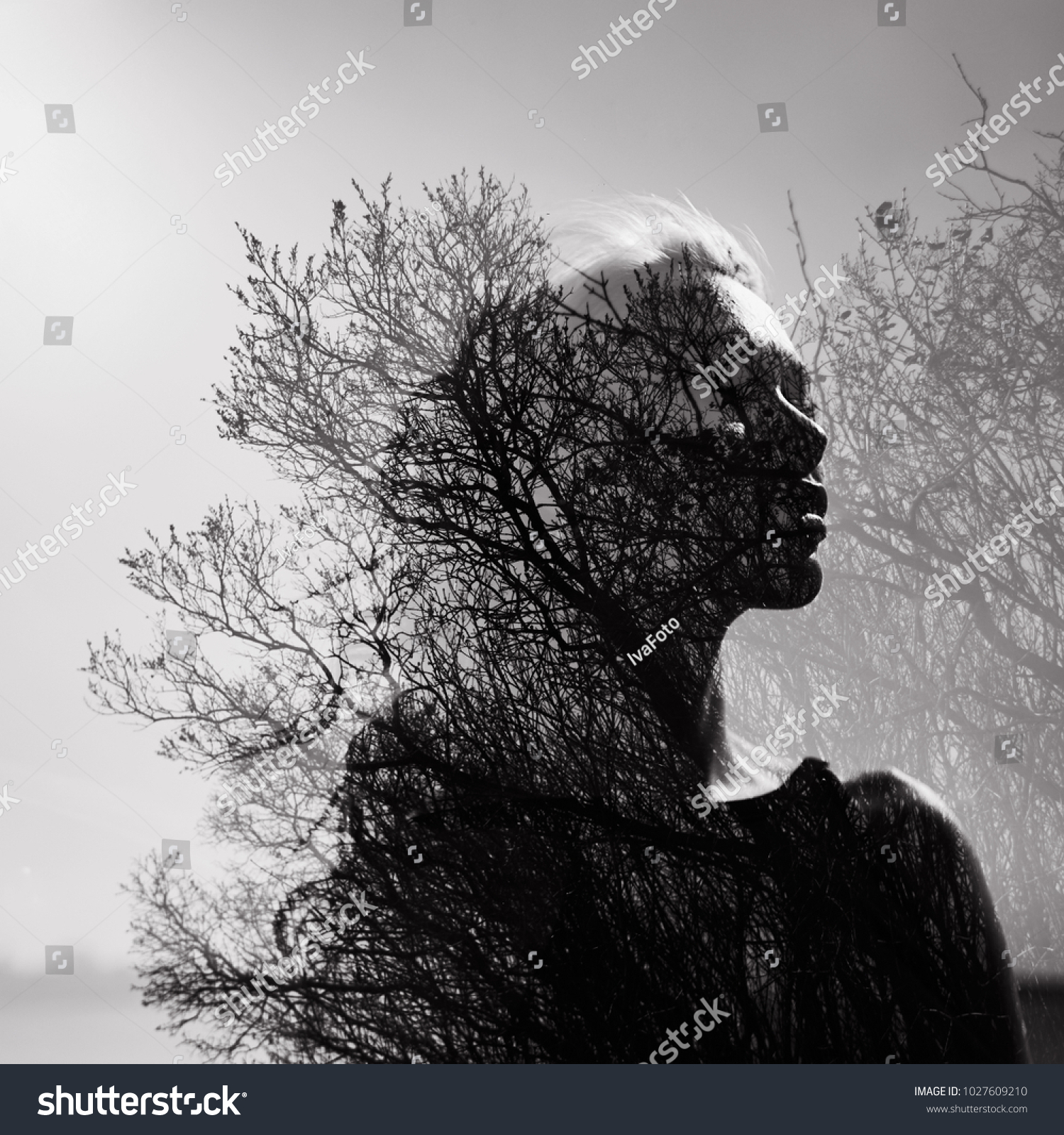 Black and white portrait of a girl with a double exposure on a background of tree