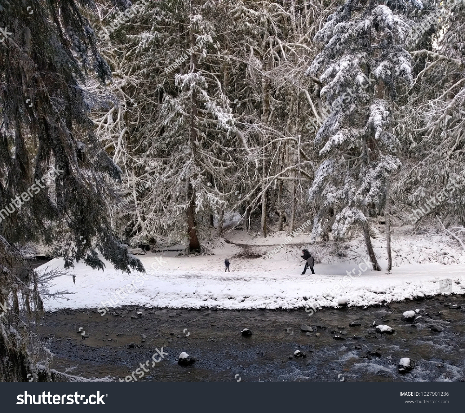 mother and child playing in snow on creek bank