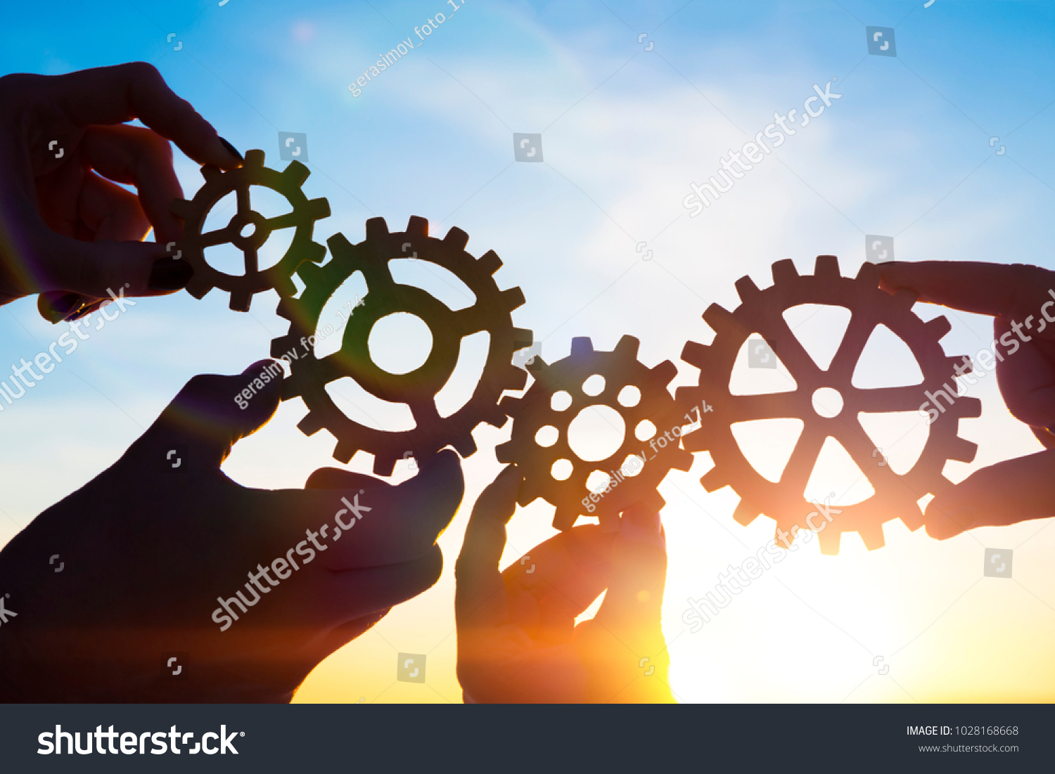 Four hands of businessmen collect gear from the gears of the details of puzzles. against the background of sunlight. The concept of a business idea. Teamwork. strategy. cooperation #1028168668