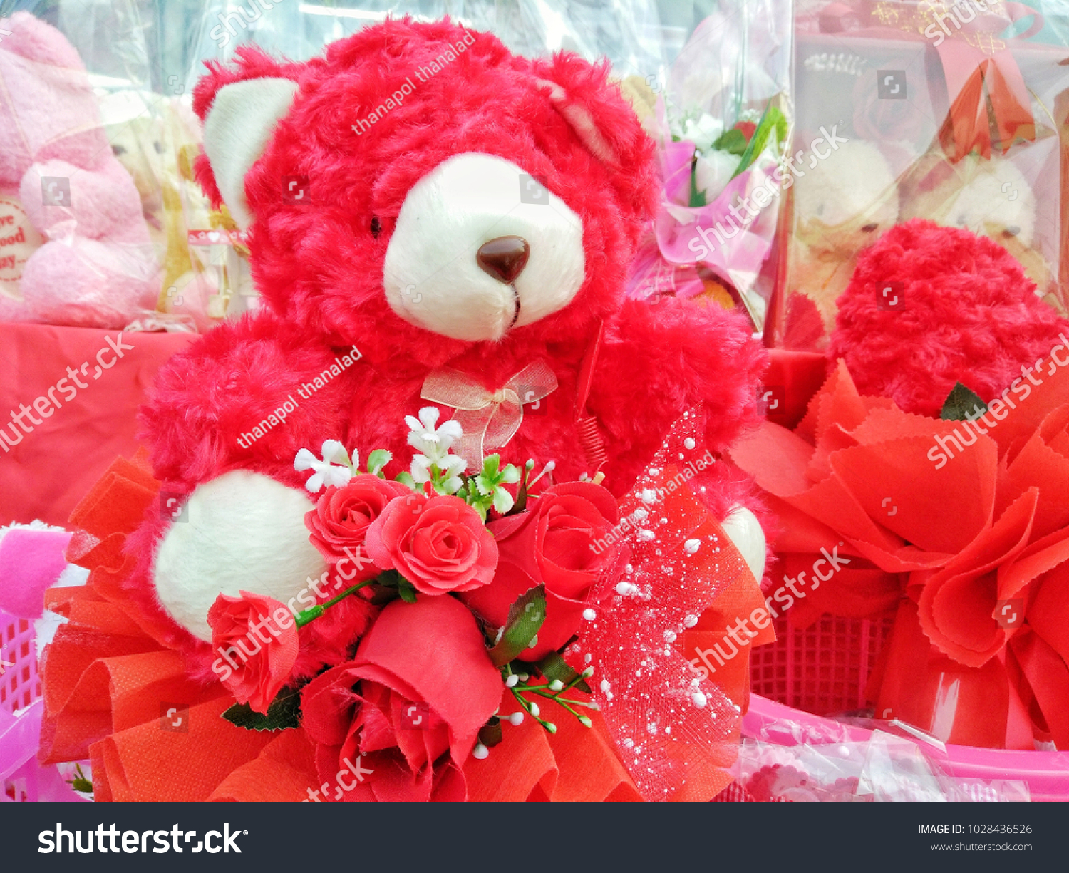 Teddy bear with red flower in the heart of Valentine's Day #1028436526