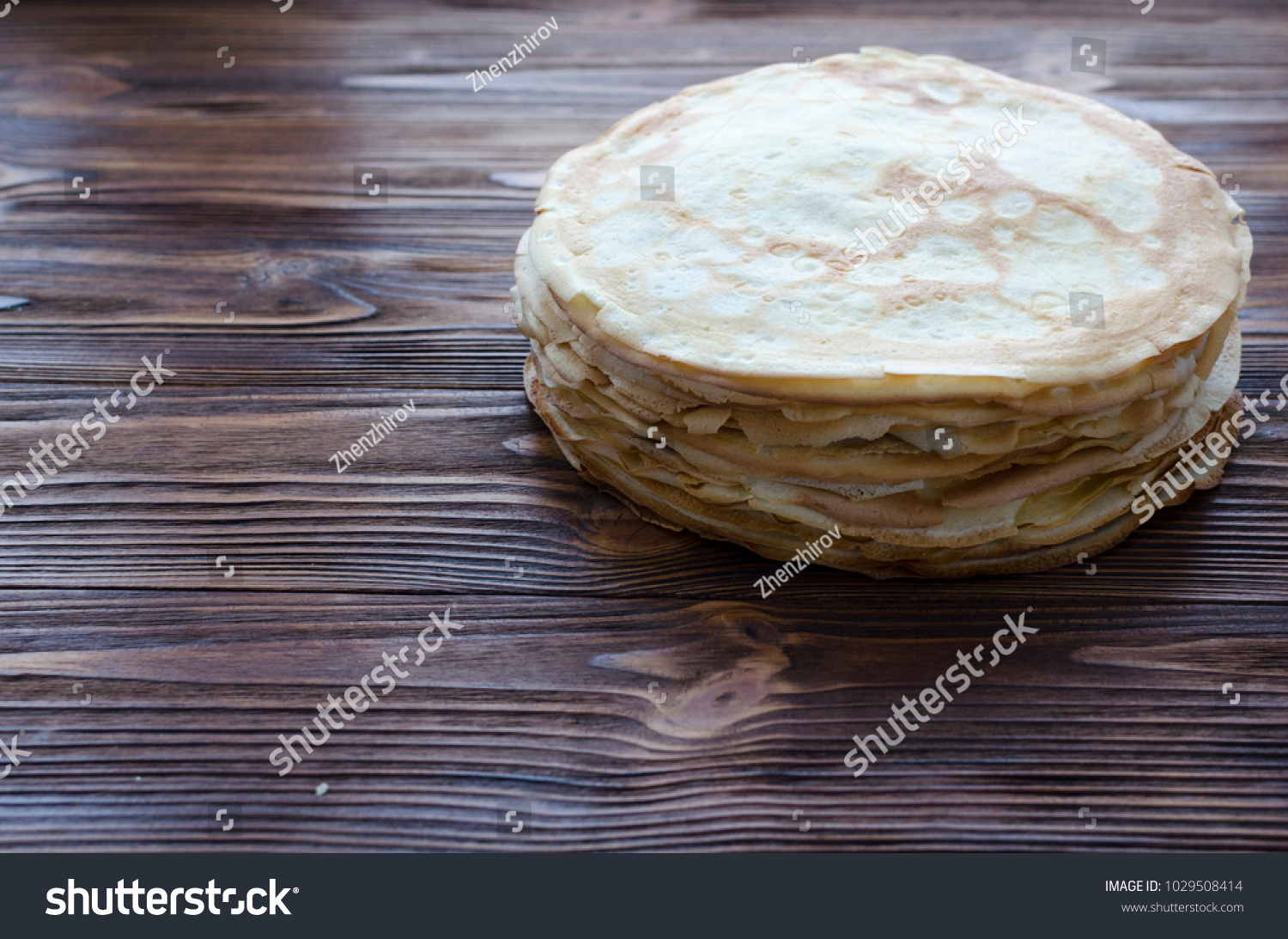 pile of pancakes on wooden background #1029508414
