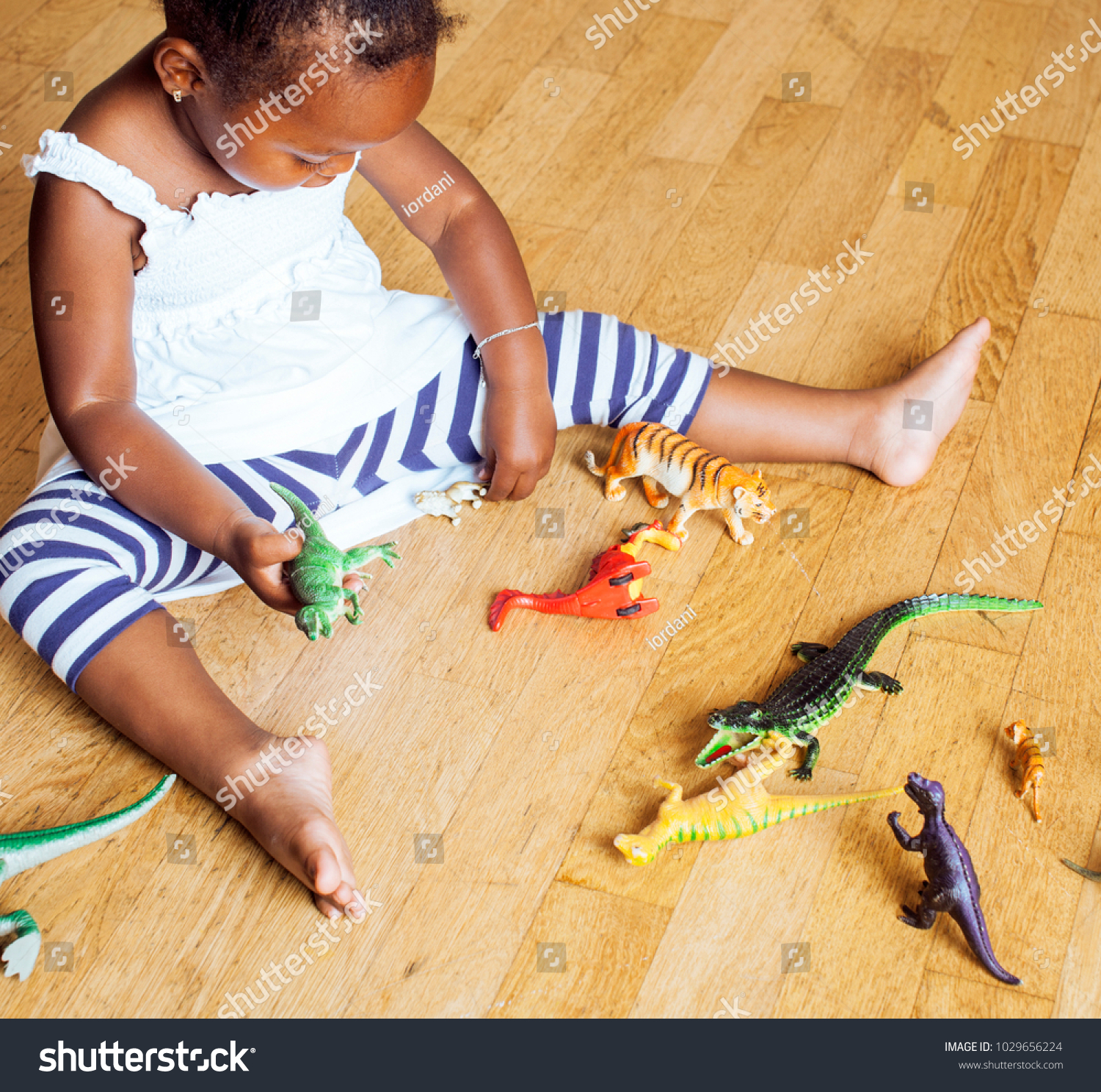 little cute african american girl playing with animal toys at ho #1029656224