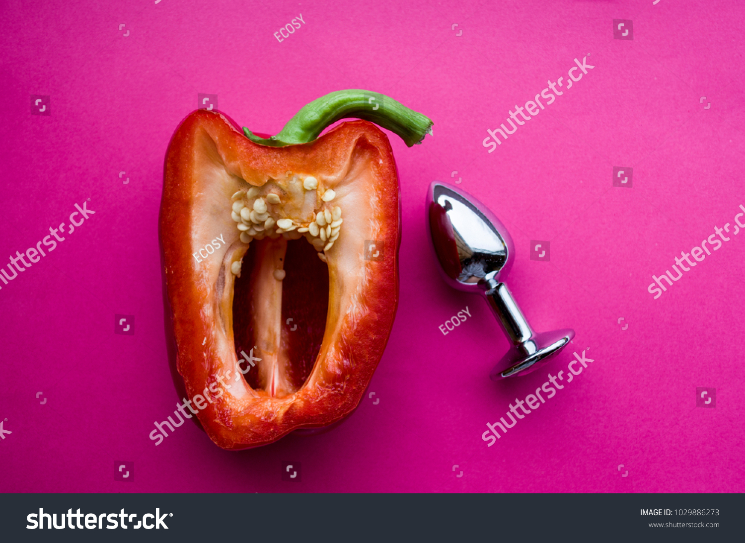 vagina symbol-sweet red pepper and anal steel plug on a pink background.  Concept