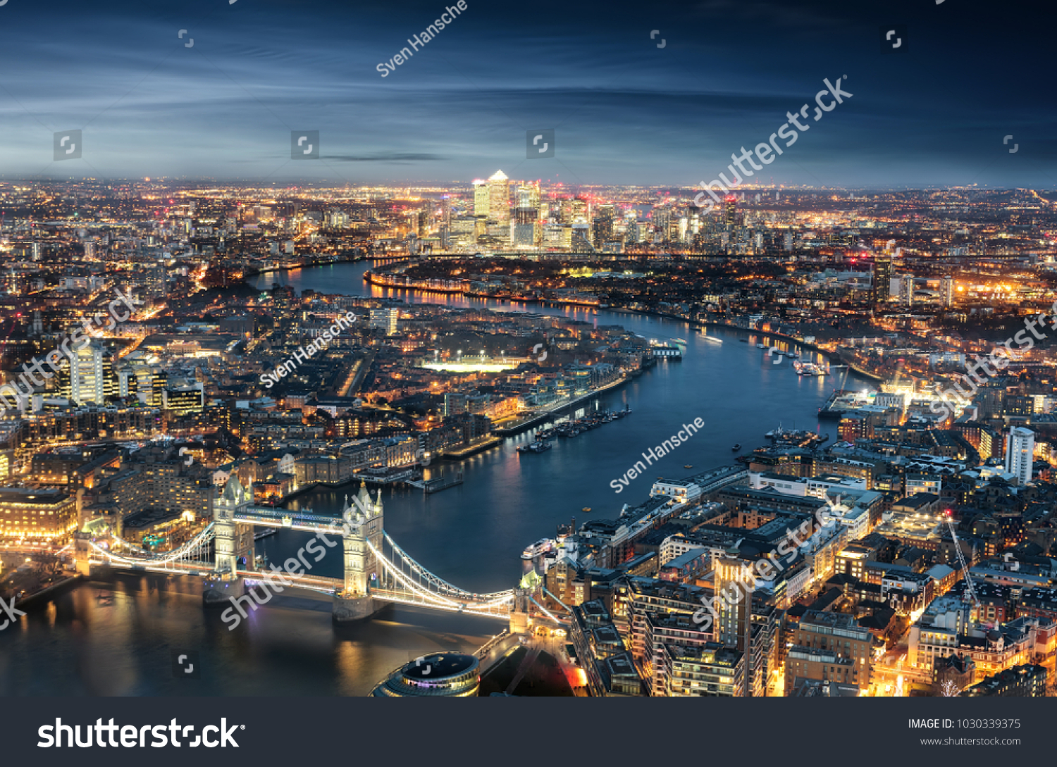 Aerial view of London: from the Tower Bridge to the financial district Canary Wharf during evening time #1030339375