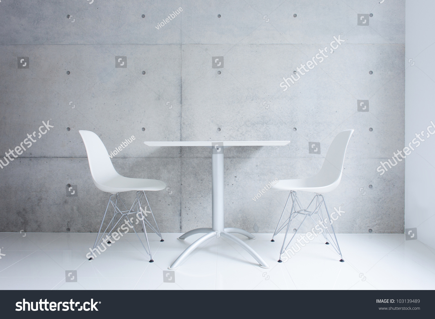 white table and chair against concrete wall stock photo 103139489 shutterstock. Black Bedroom Furniture Sets. Home Design Ideas
