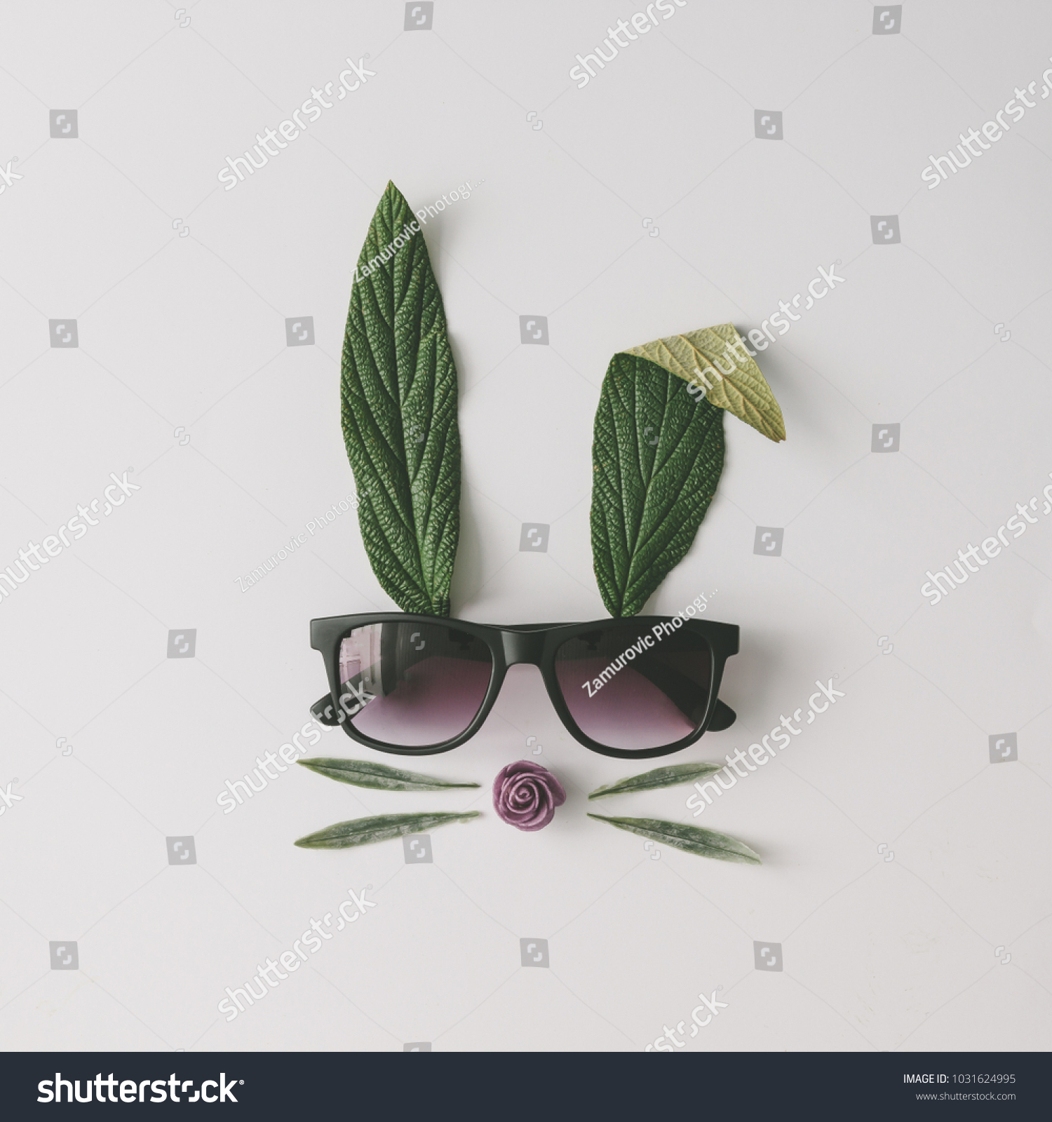 Bunny rabbit face made of natural green leaves with sunglasses on bright background. Easter minimal concept. Flat lay. #1031624995 - 123PhotoFree.com