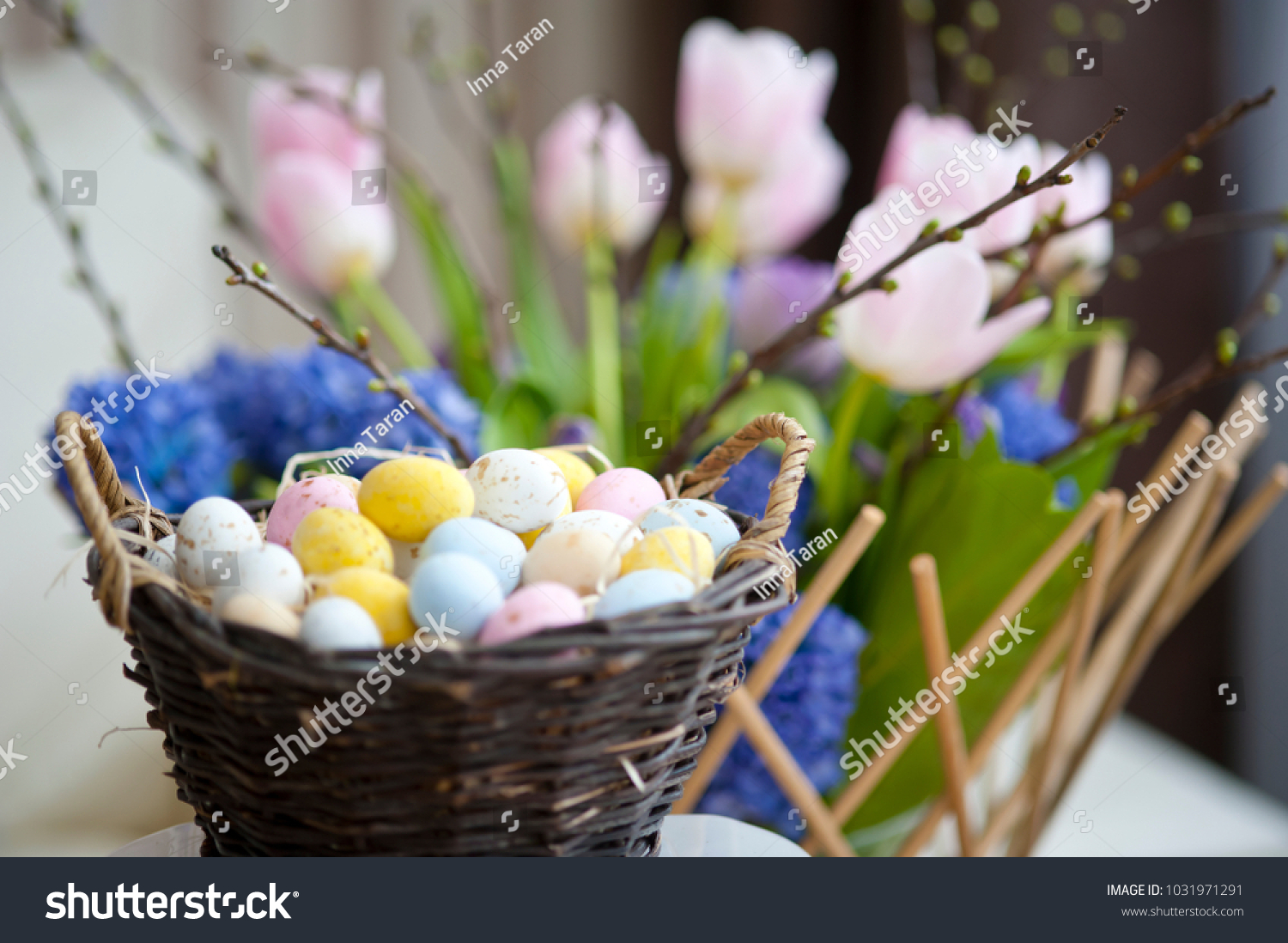 Easter eggs in a basket on a background of spring flowers, Easter breakfast