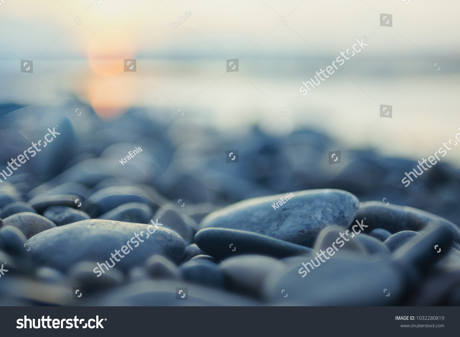 Pebble stones on the shore close up in the blurry sunset light in the distance  background.