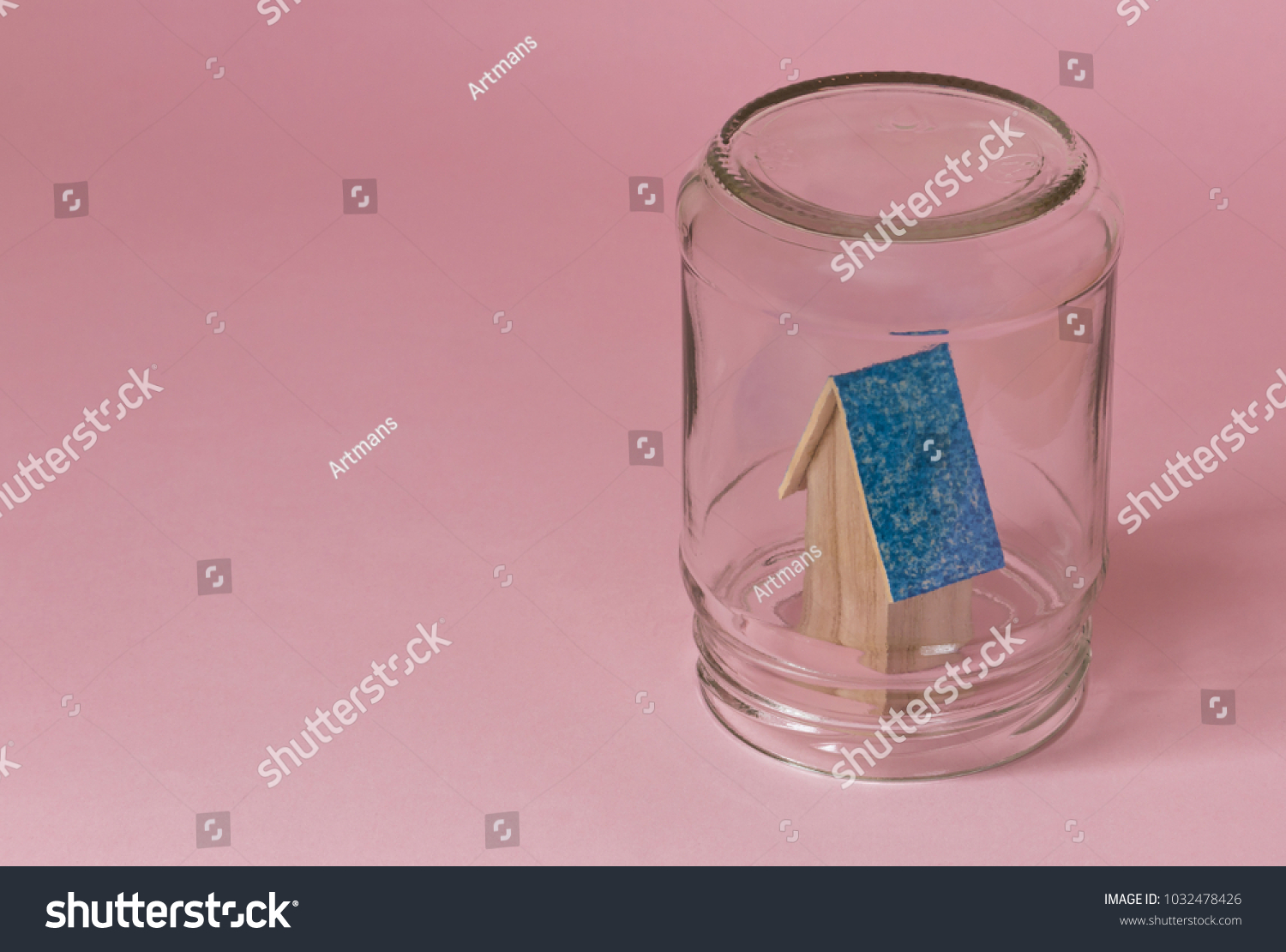 House in a jar protected in safety. Protected from misfortunes. House in a jar on a pink background with a blue roof. #1032478426