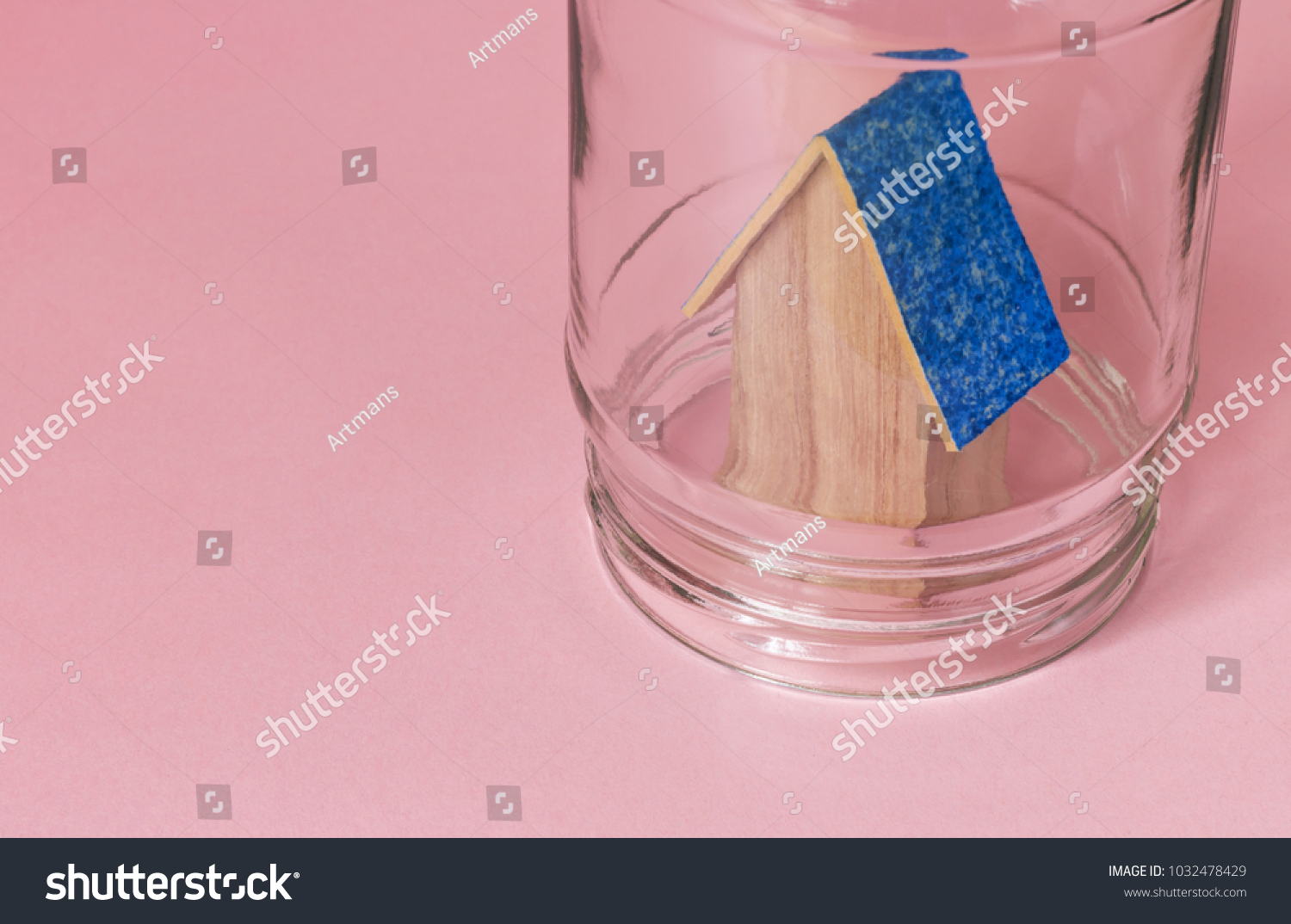 House in a jar protected in safety. Protected from misfortunes. House in a jar on a pink background with a blue roof. #1032478429