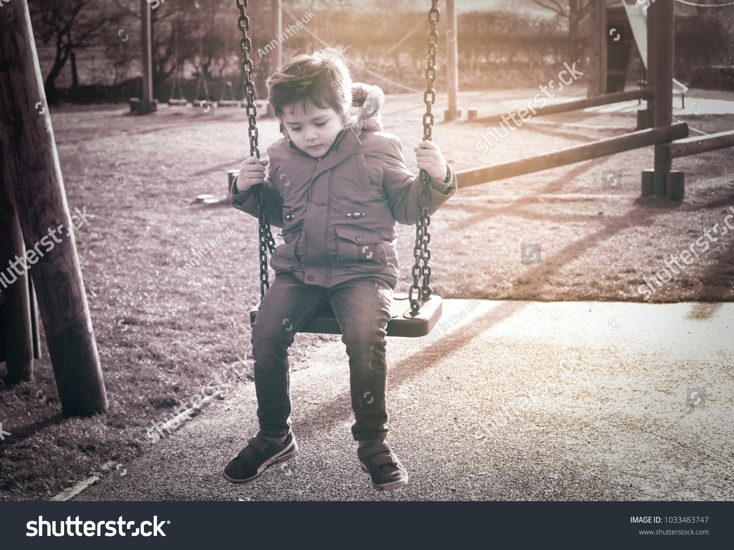Lonely child with a sad face sitting alone on swing in the playground in retro filter