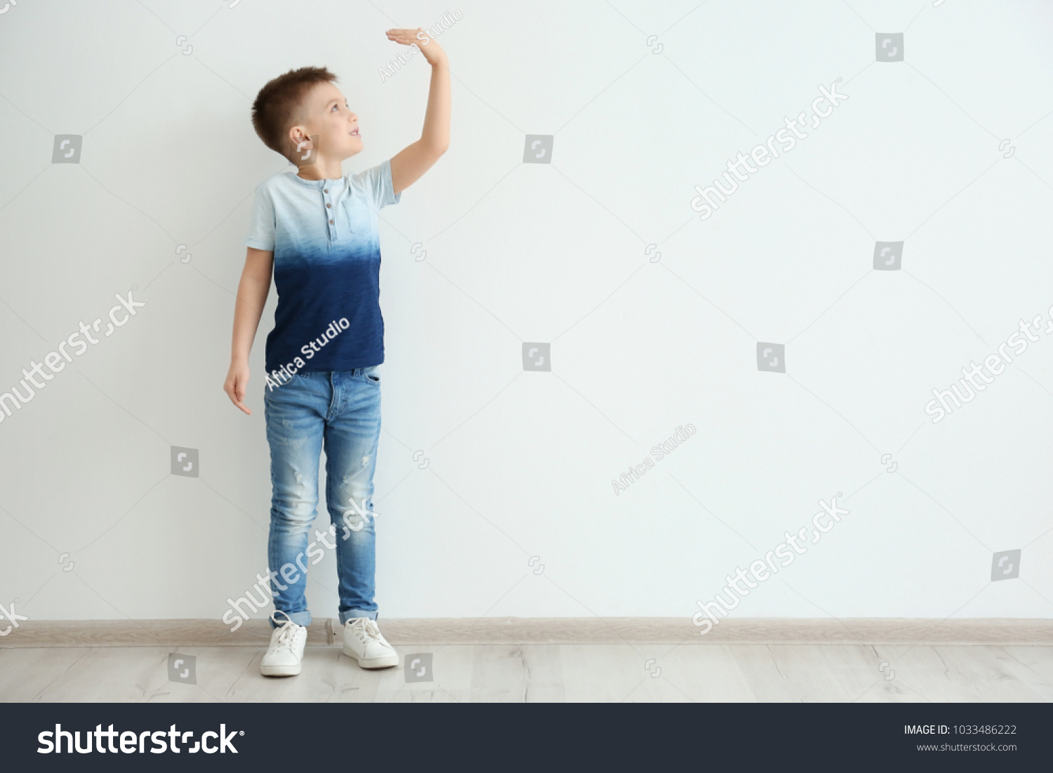 Little boy measuring height near light wall #1033486222