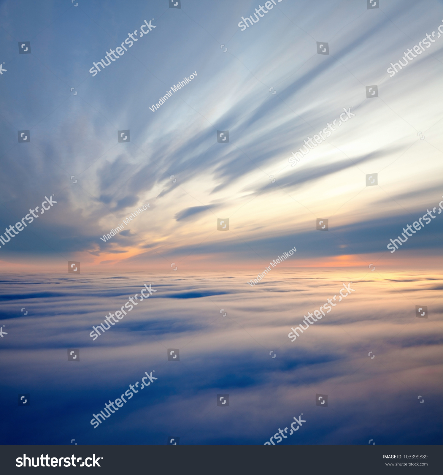 Aerial view of a cloudy sunset while flying above the clouds stock