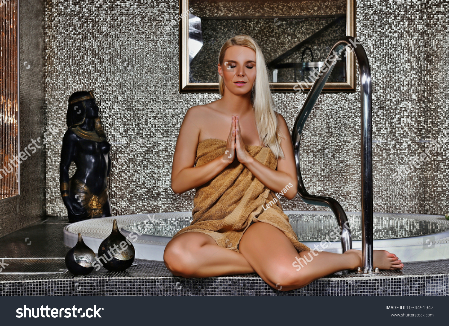 bbd8e15de Beautiful woman wearing towel sitting in a yoga position with hands  together