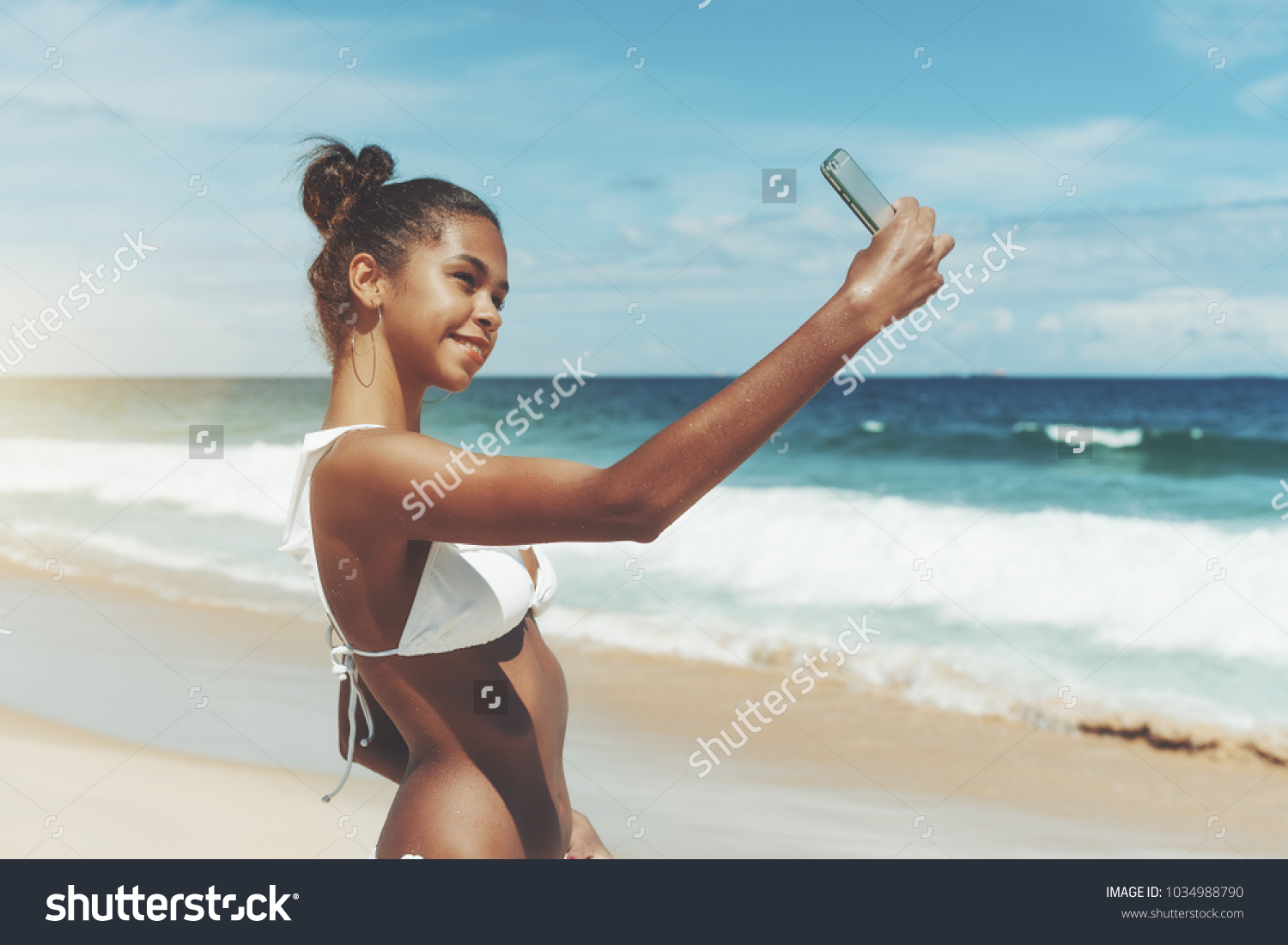 Young sexy Brazilian model girl is taking selfie while standing on the  ocean beach after swimming