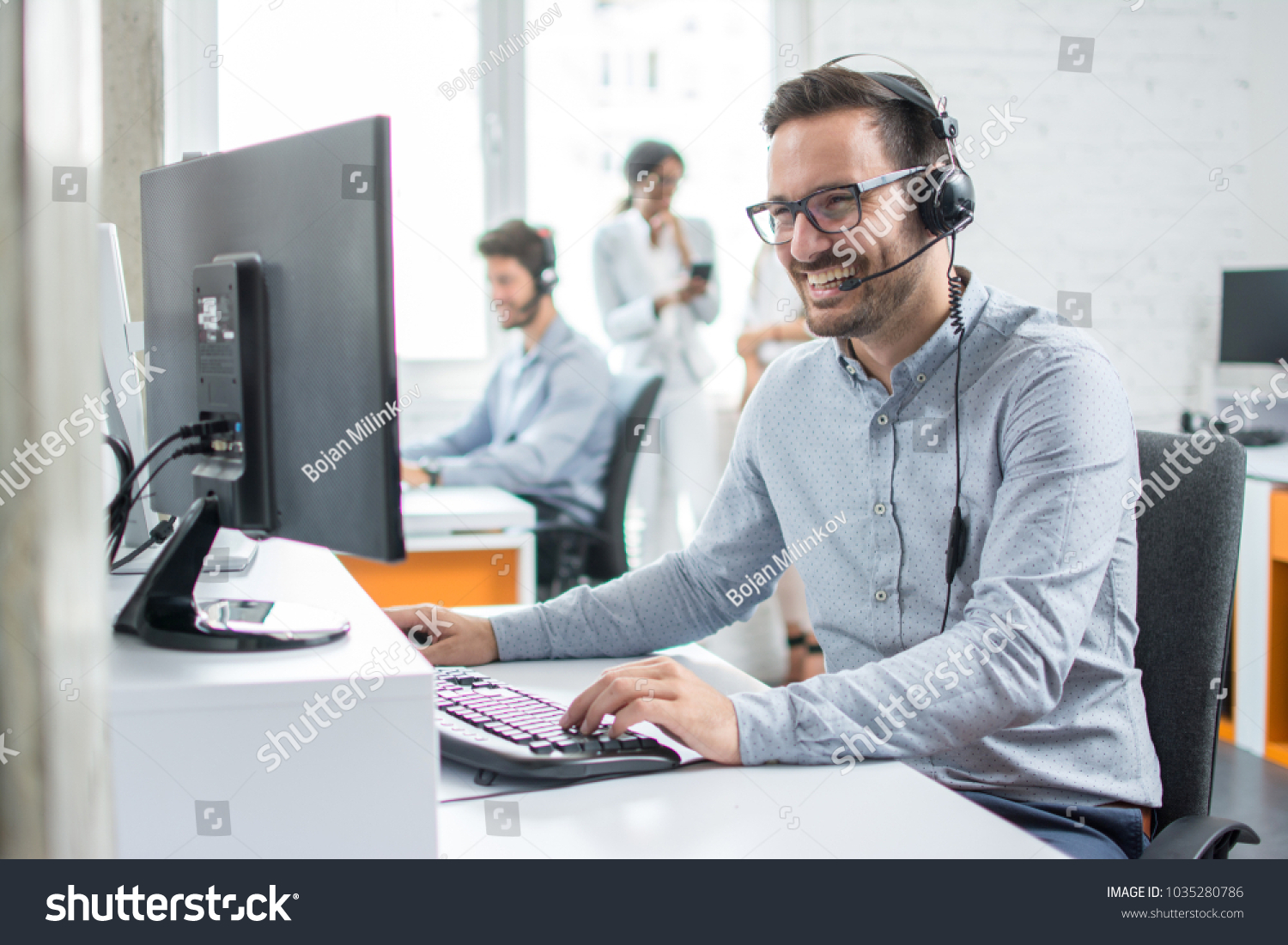 Smiling customer support operator with hands-free headset working in the office. #1035280786