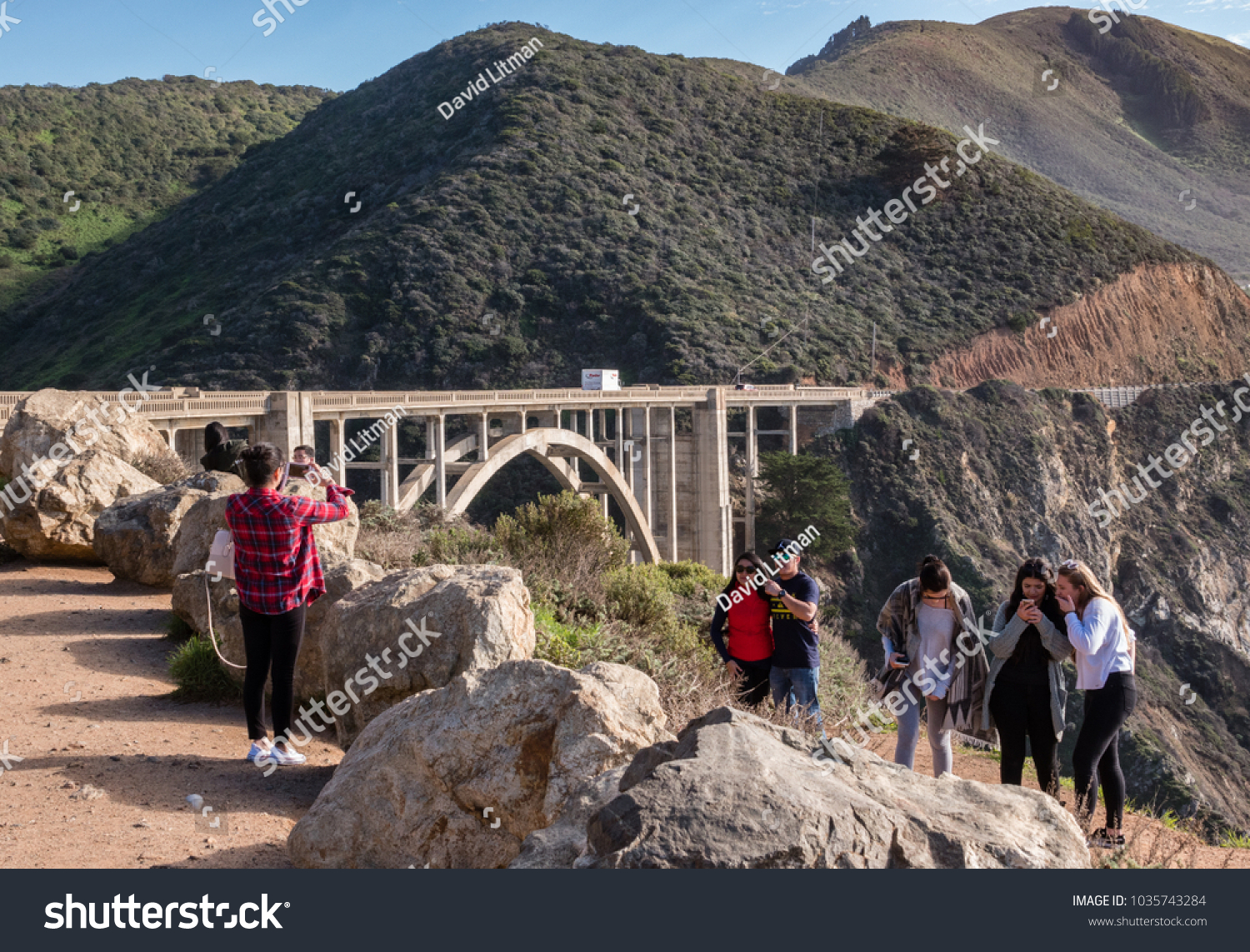 Big Sur, California - January 31, 2018: Tourists take photos and check selfies at scenic viewpoint next to Bixby Bridge, along the Pacific Coast of the Monterey Bay on Highway 1.  California travel.