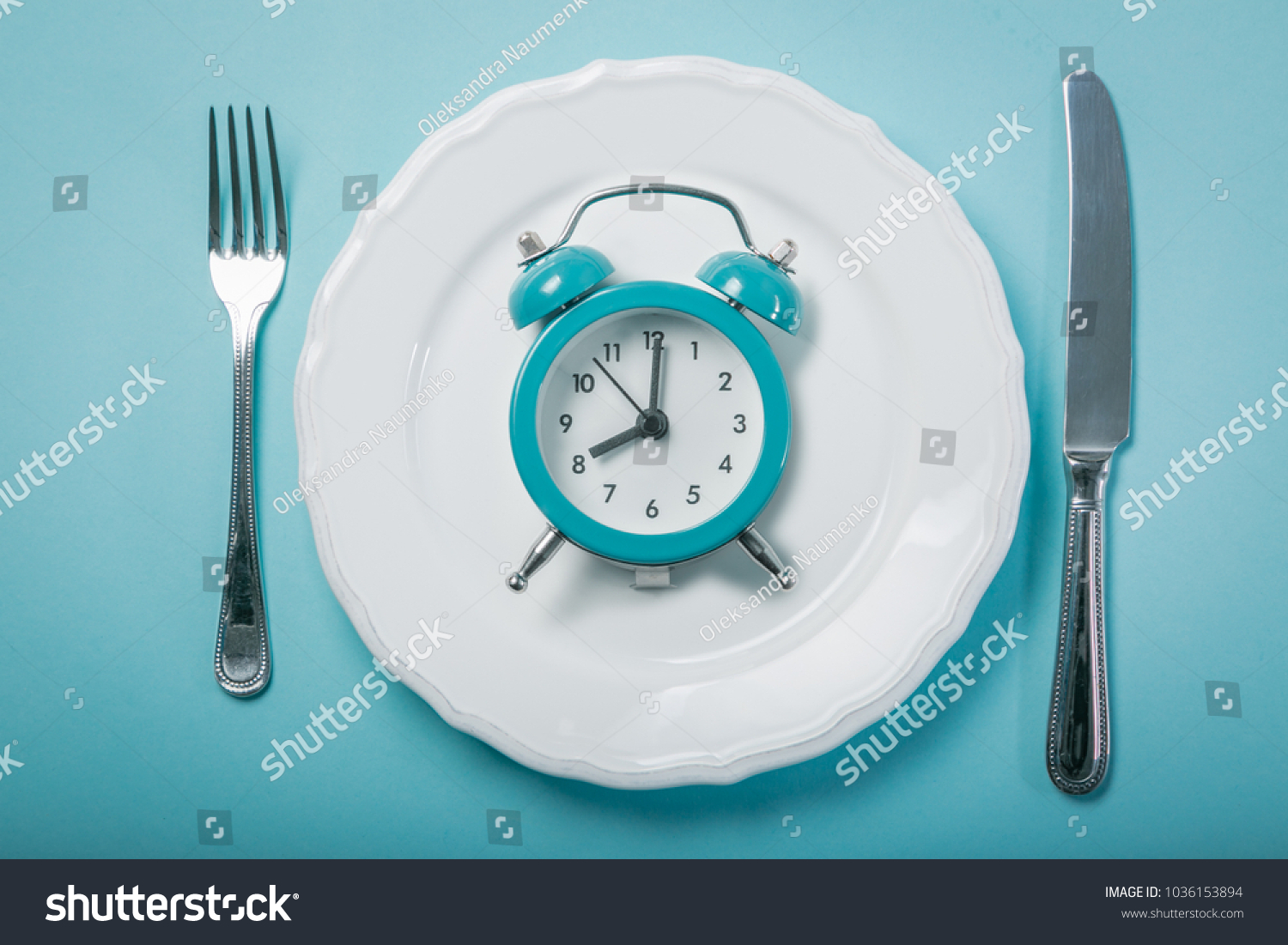 Intermittent fastin concept - empty plate on blue background #1036153894