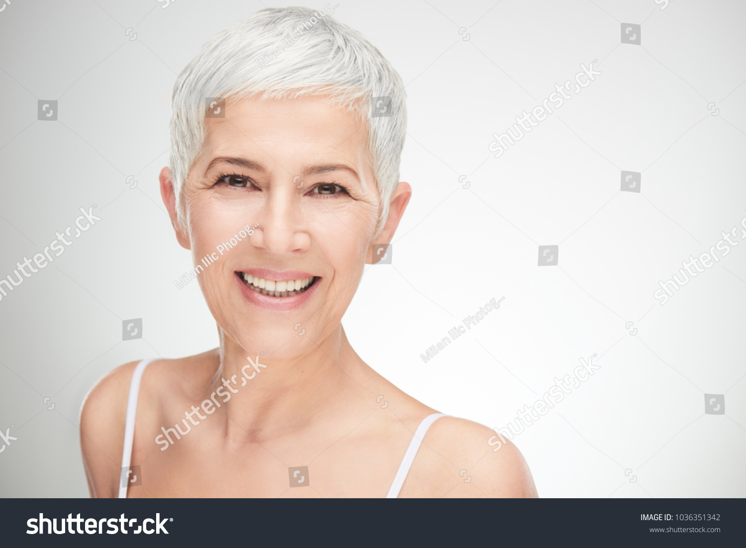 Portrait of beautiful senior woman in front of white background. #1036351342