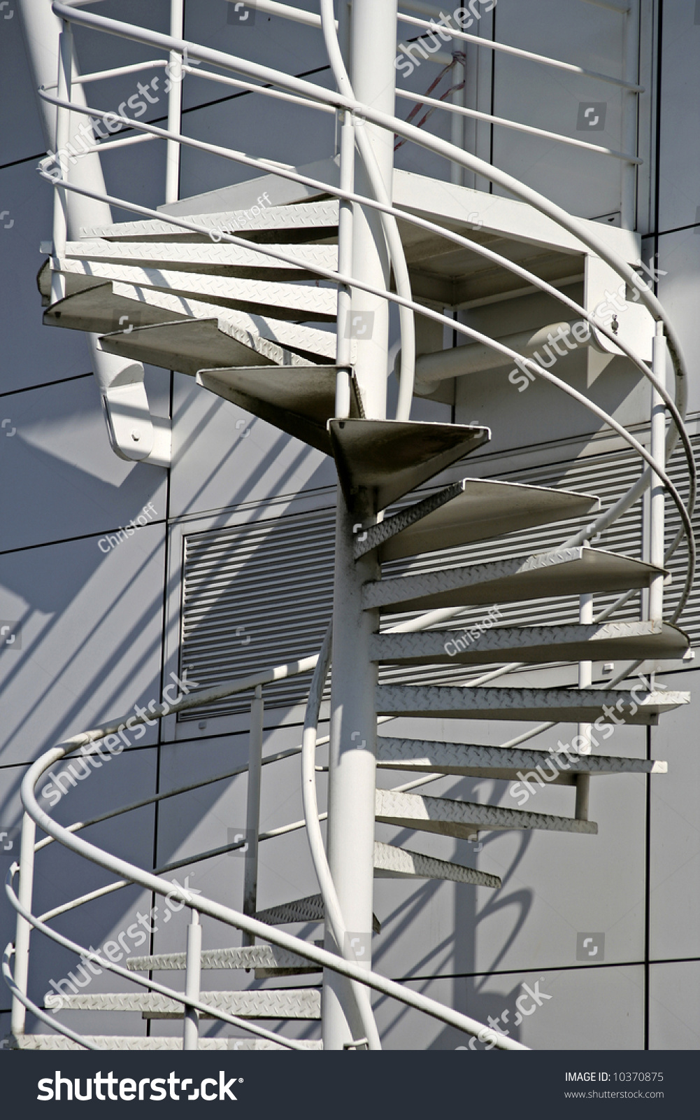 Metal white spiral stairs on the outside of a factory for Aluminum spiral staircase prices