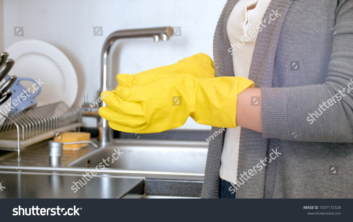 Closeup image of young housewife taking off yellow rubber gloves #1037172328