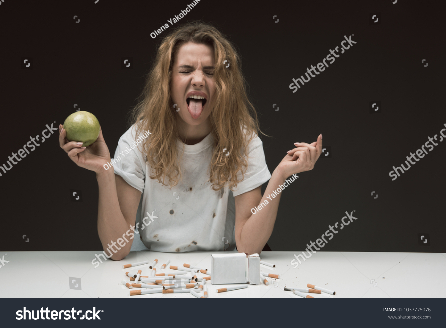 Waist up portrait of stressed blonde girl with apple making wry face in  disgust, cigarettes