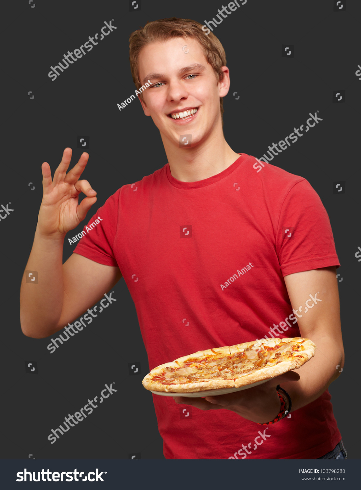 portrait of a young man holding a pizza and doing a good. Black Bedroom Furniture Sets. Home Design Ideas