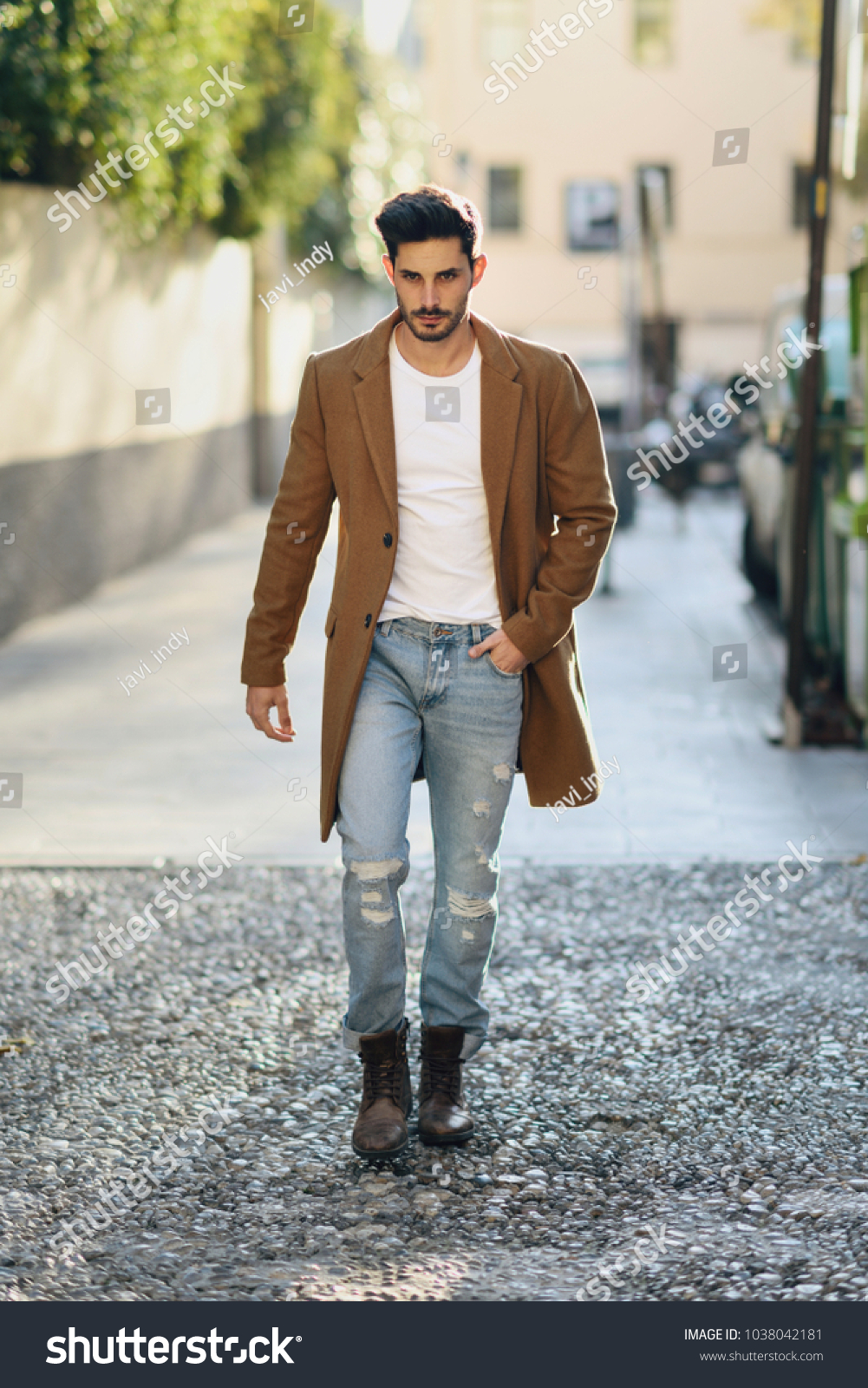 Young man wearing winter clothes in the street. Young bearded guy with  modern hairstyle with