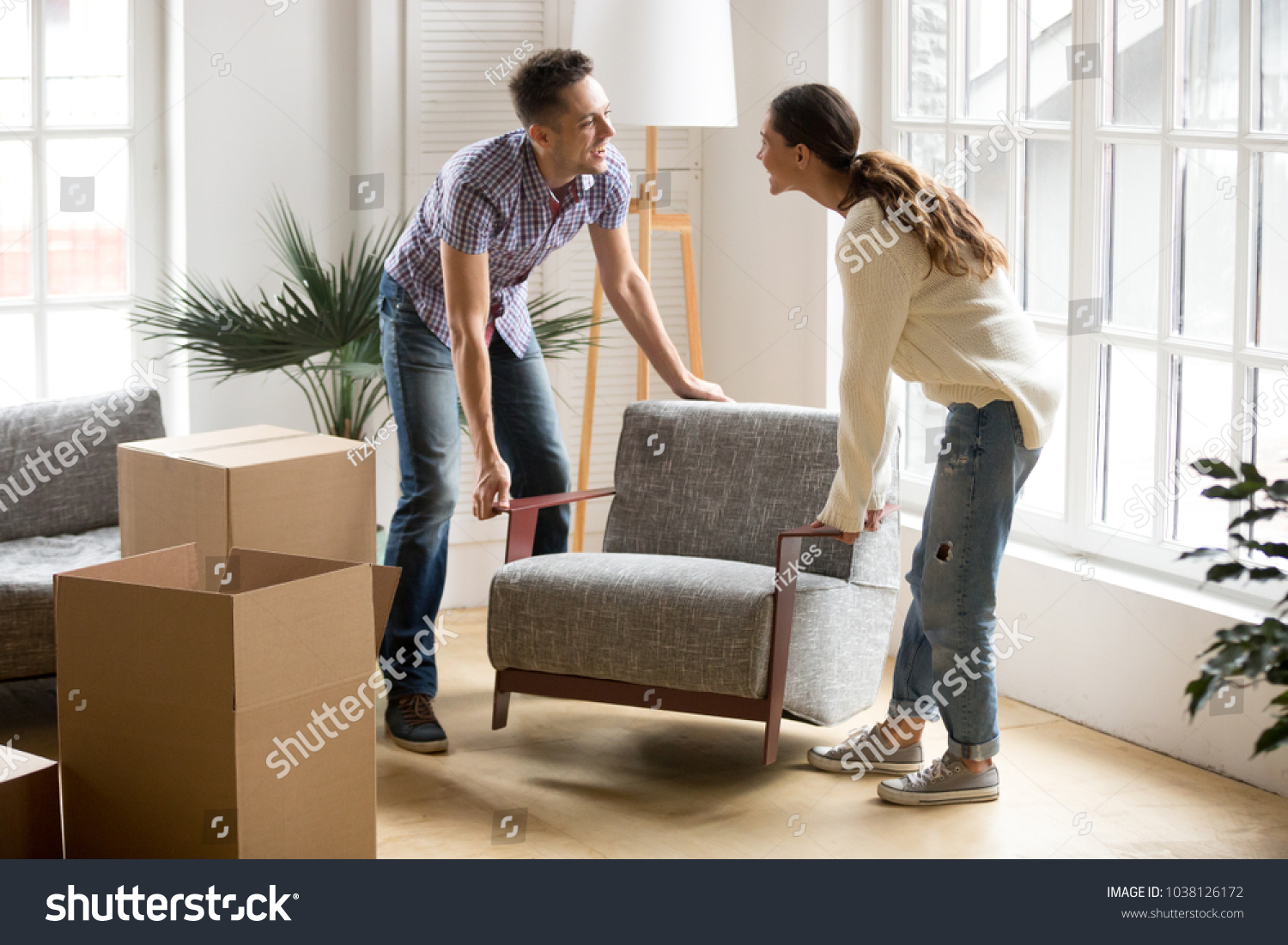 Smiling couple carrying modern chair together placing furniture moving into new home, young family discussing house improvement interior design while furnishing living room, remodeling and renovation #1038126172
