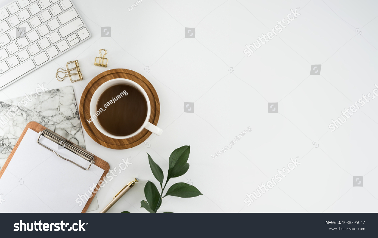 Flat lay, top view office table desk. Workspace with blank clip board, keyboard, office supplies, pencil, green leaf, and coffee cup on white background. #1038395047