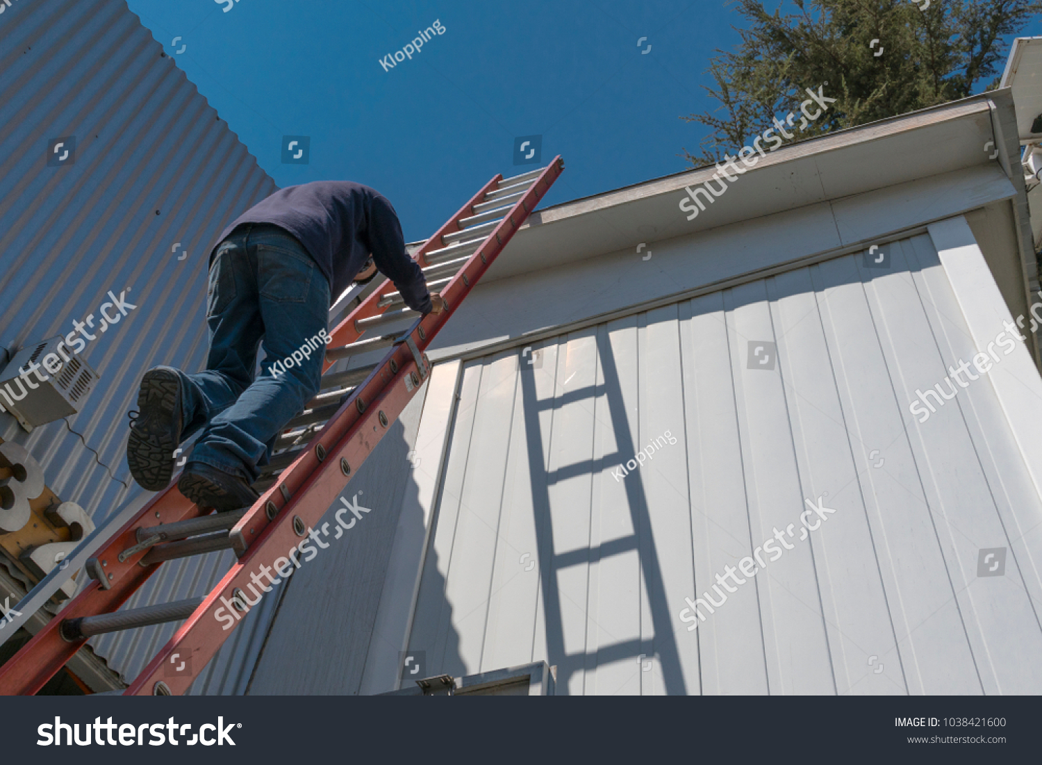 Climbing the risks of a worker by ladder to work on the roof of a house on a beautiful sunny day. #1038421600