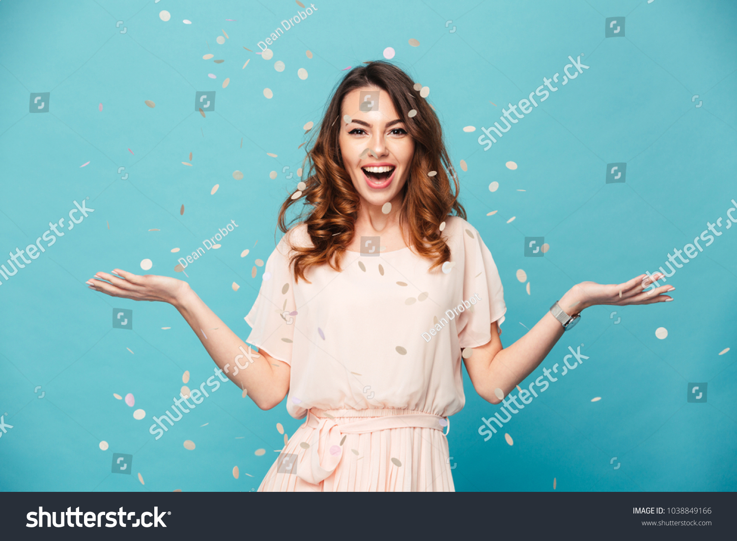 Portrait of a cheerful beautiful girl wearing dress standing standing under confetti rain and celebrating isolated over blue background
