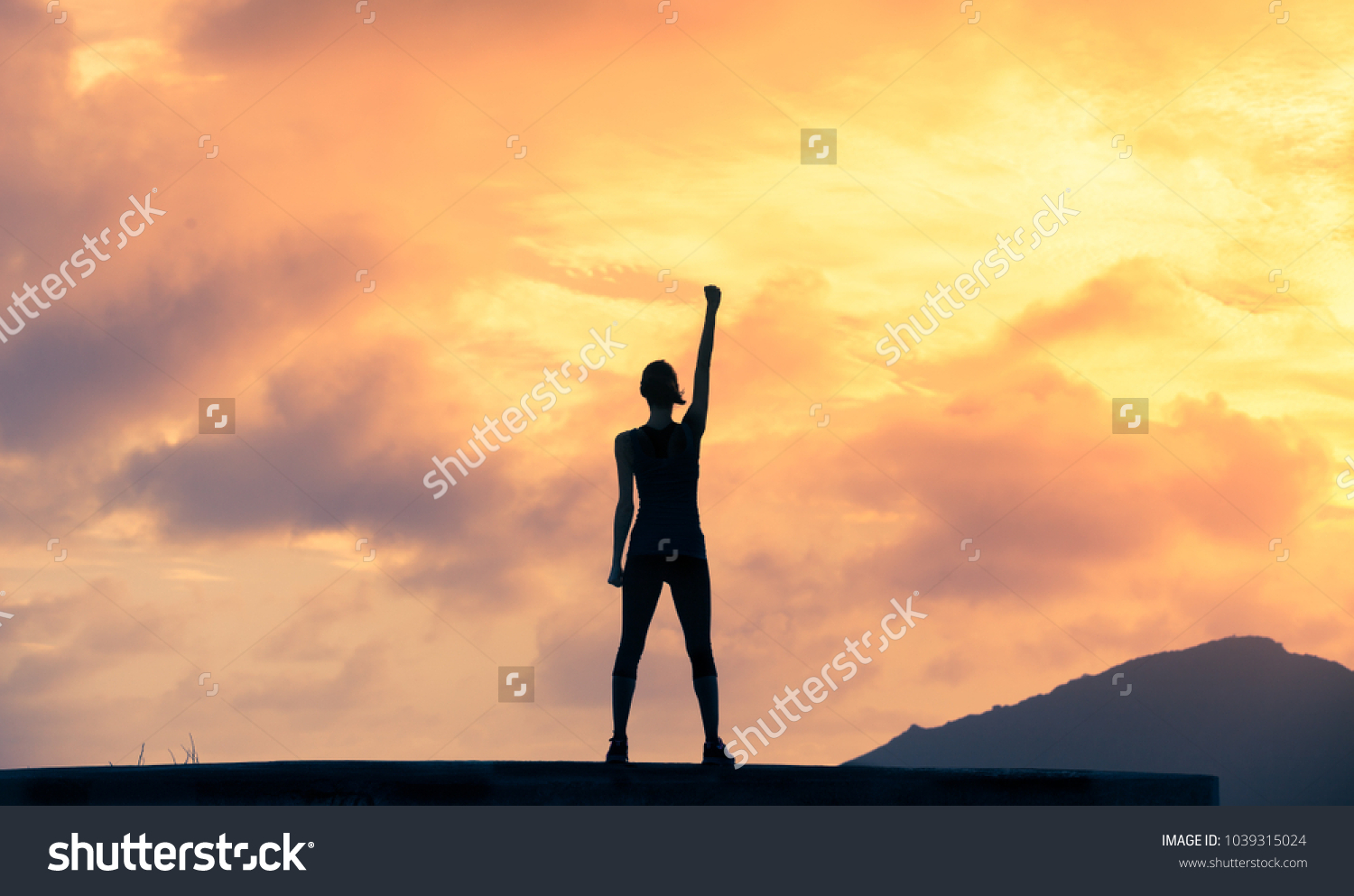 Stand strong. Woman with fist in the air. Feeling motivated, strength and courage concept.  #1039315024