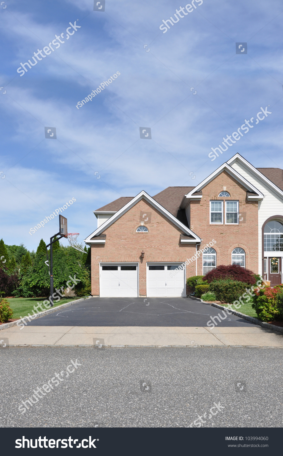 Basketball hoop on empty blacktop driveway double car for Double story garage