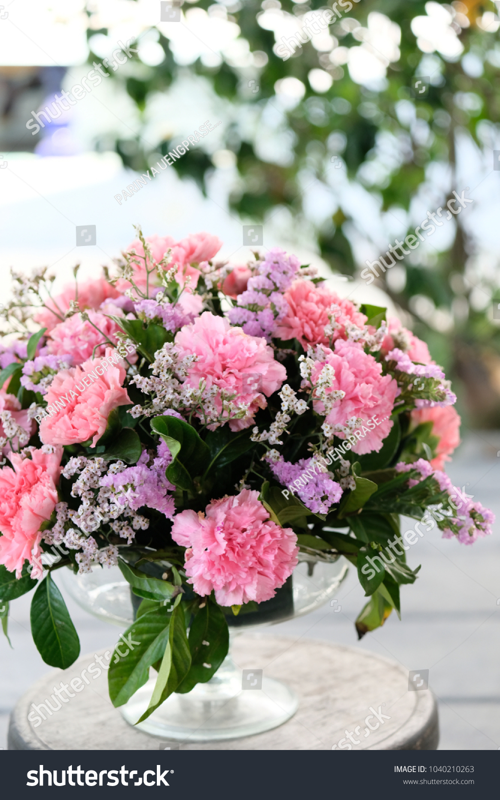 Bouquet Of Pink Carnations Flowers And Green Leaves In Glasses Vase