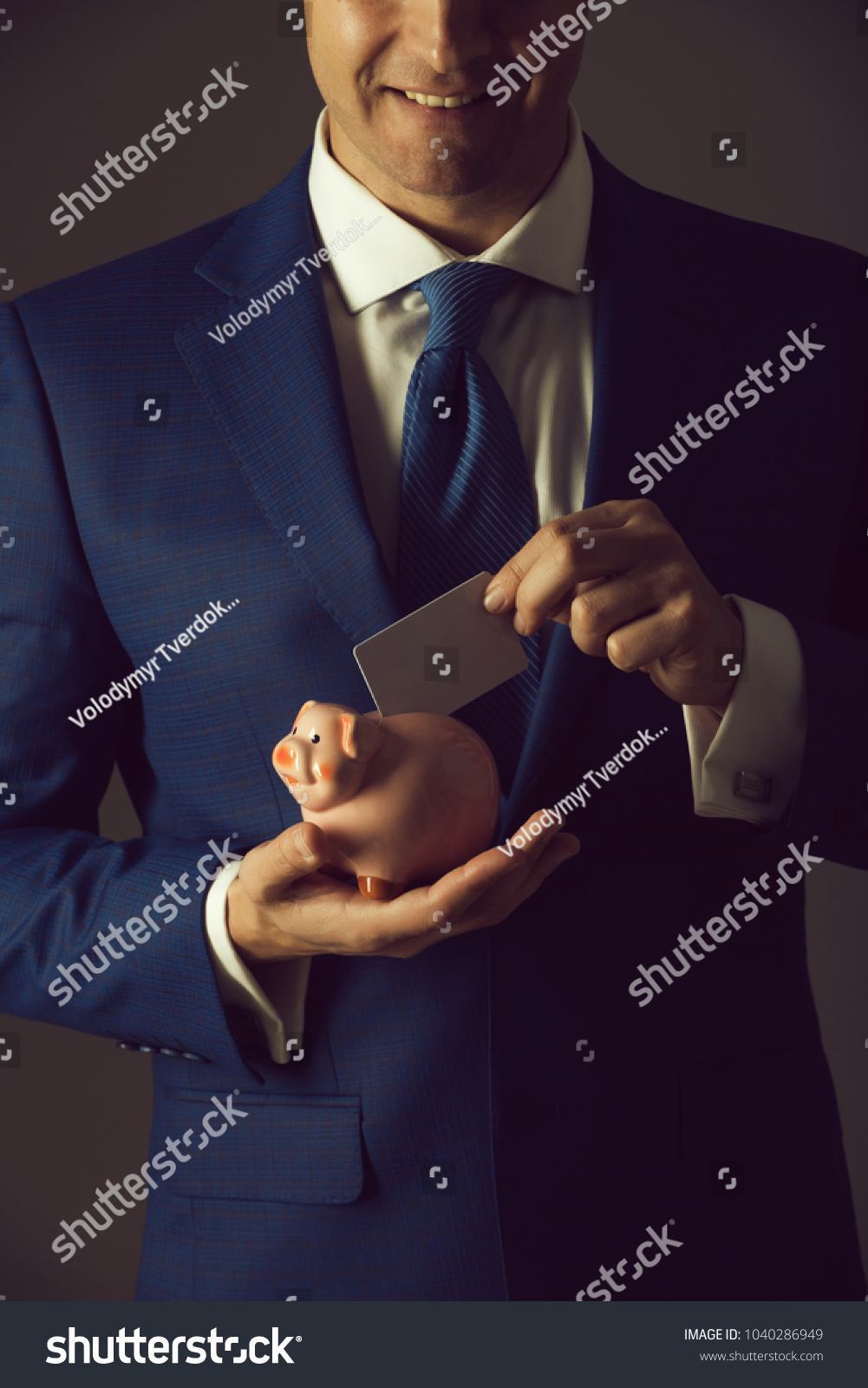 Hands Putting Blank Business Card In Piggy Bank For Saving On Grey  Background. Stylish Formal
