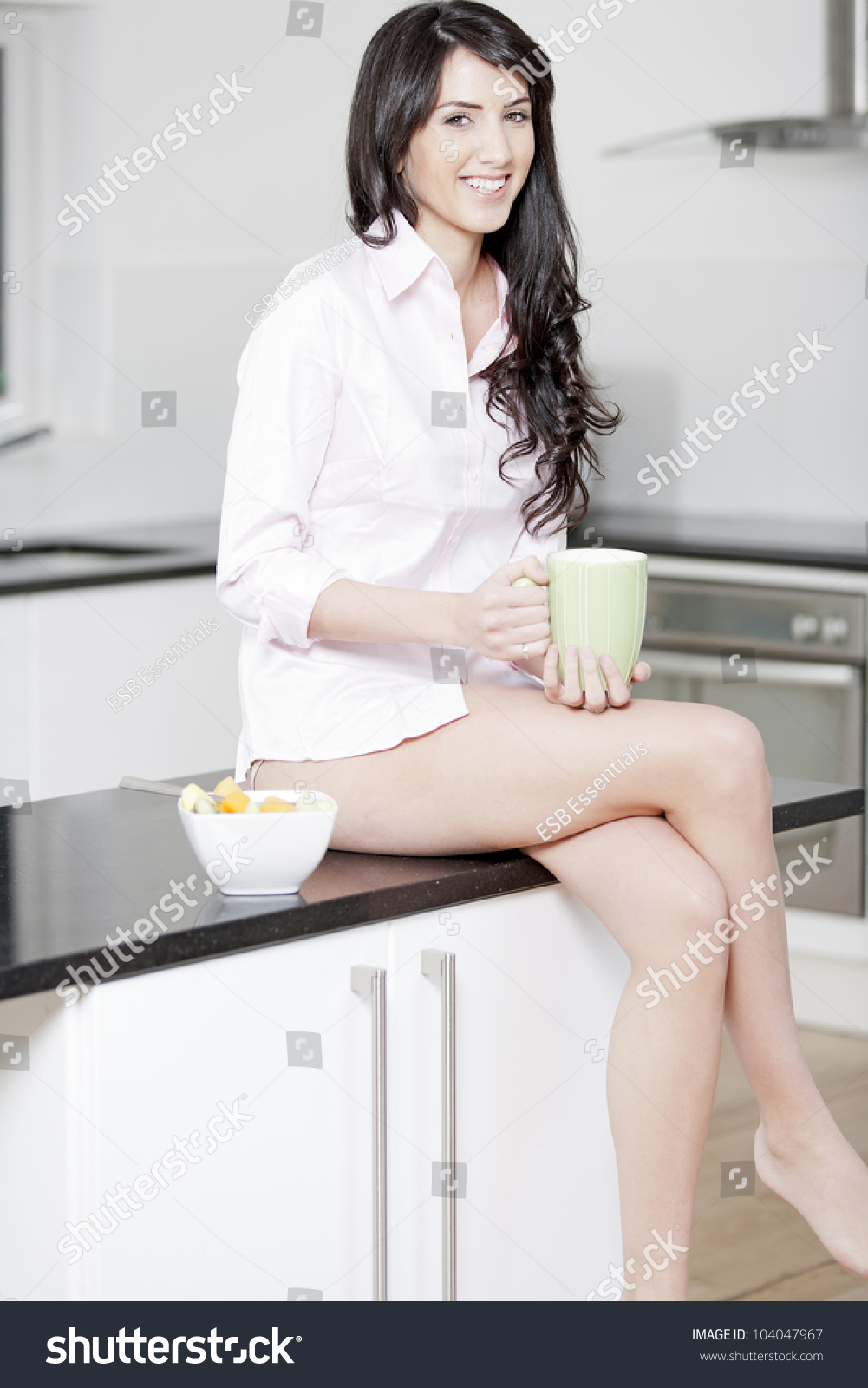 d0f711cf8f2d Young woman in underwear and pink shirt sat in kitchen eating breakfast
