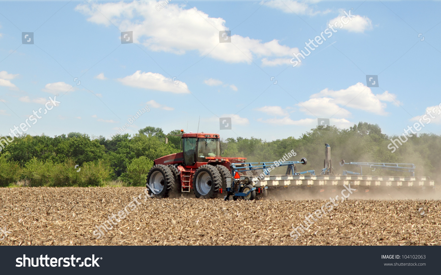Tractor In Field Planting : Red tractor planting crop farm field stock photo