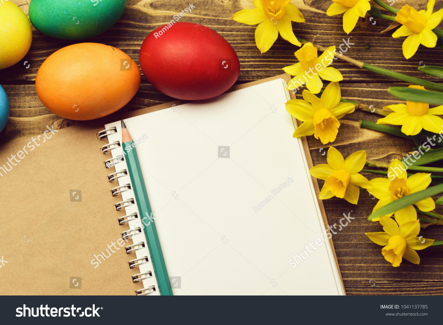 Drawing pencil and paper notebook colorful painted eggs spring yellow narcissus flower on wooden