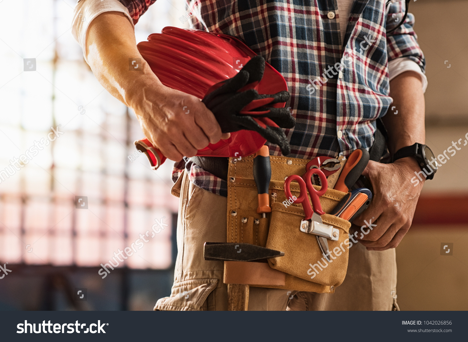 Closeup of bricklayer hands holding hardhat and construction equipment. Detail of mason man hands holding work gloves and wearing tool kit on waist. Handyman with tools belt and artisan equipment. #1042026856