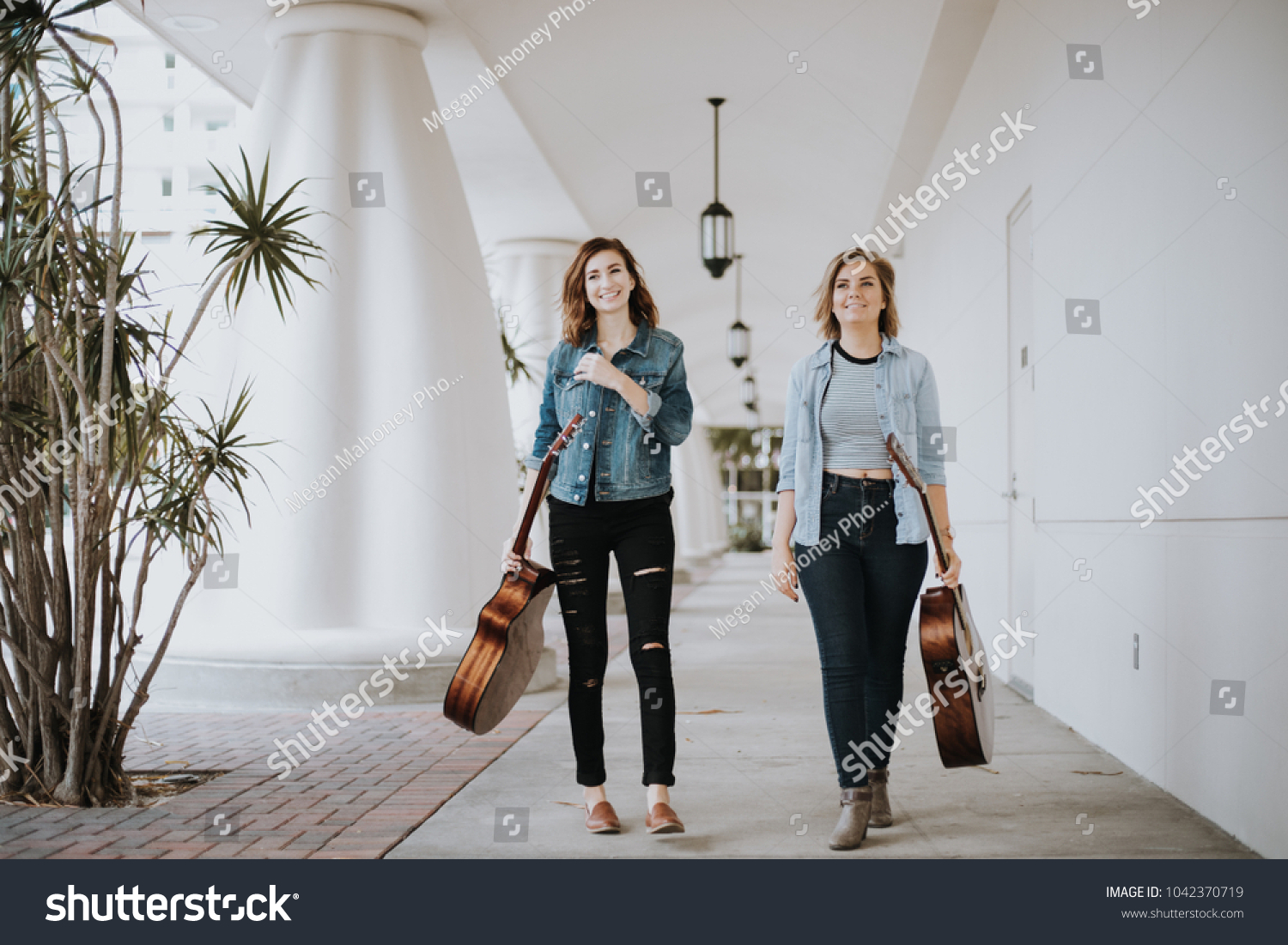 Pretty Female Musicians Walking Down Outdoor Corridor