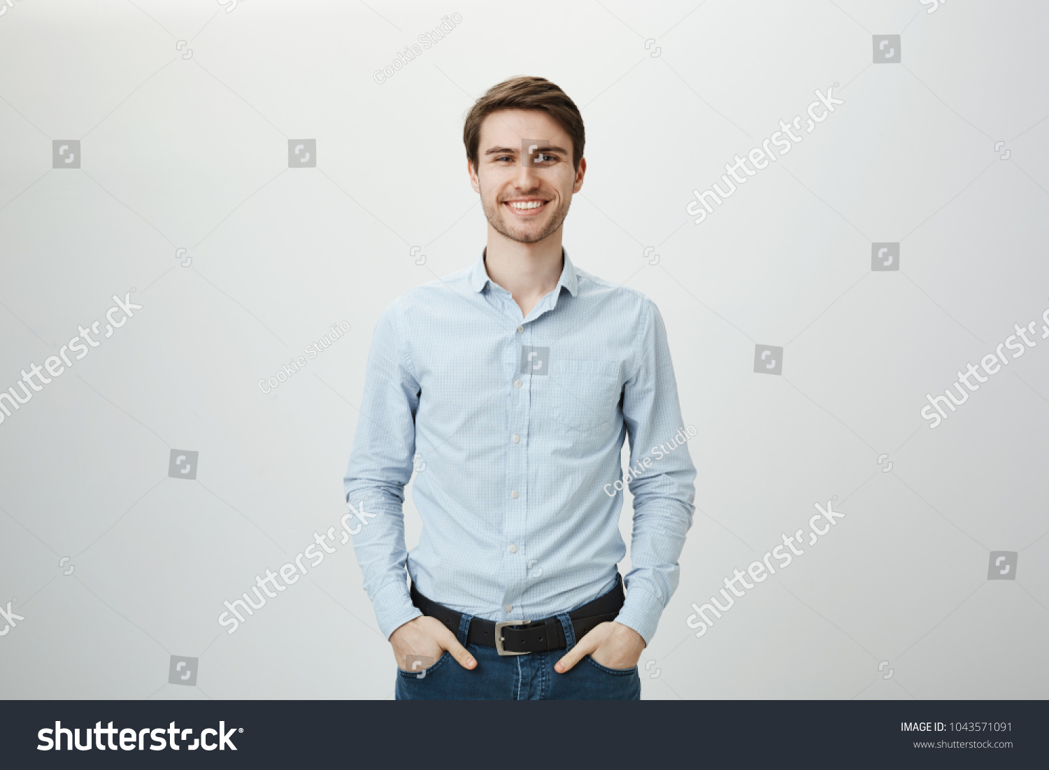 Confidence and business concept. Portrait of charming successful young entrepreneur in blue-collar shirt, smiling broadly with self-assured expression while holding hands in pockets over gray wall #1043571091