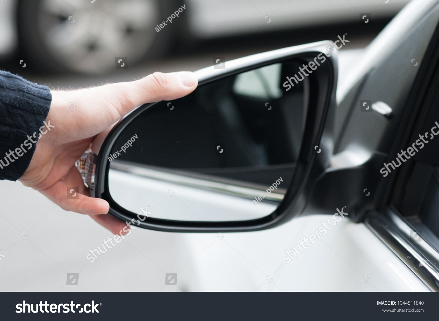 Young human hand is preparing or correct car mirror for the trip or travel from car window. #1044511840
