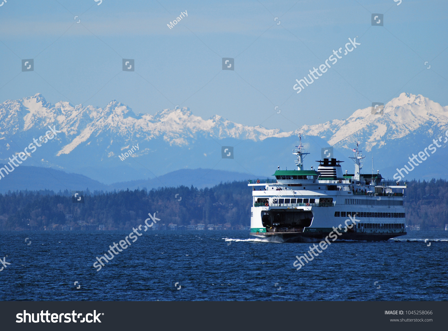 Washington State Ferry cruises in front of Olympic Mountains on approach to Seattle #1045258066