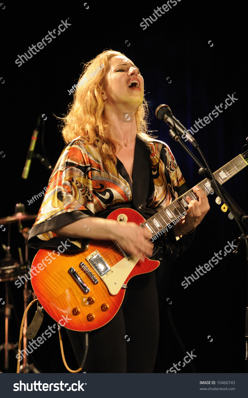 Attractive Singing Female Guitarist Playing At A Life Concert