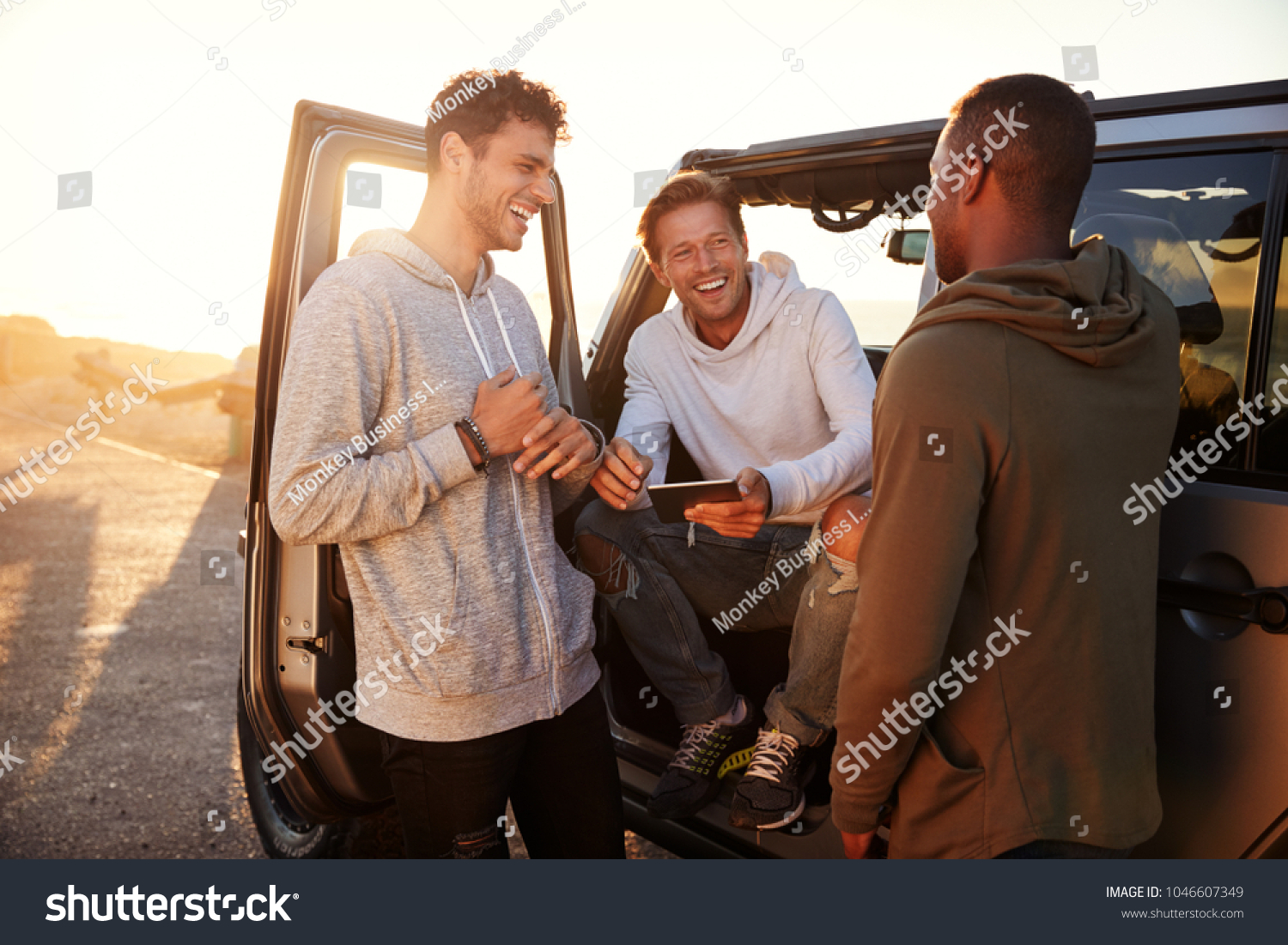 Three male friends on a road trip using a tablet computer #1046607349