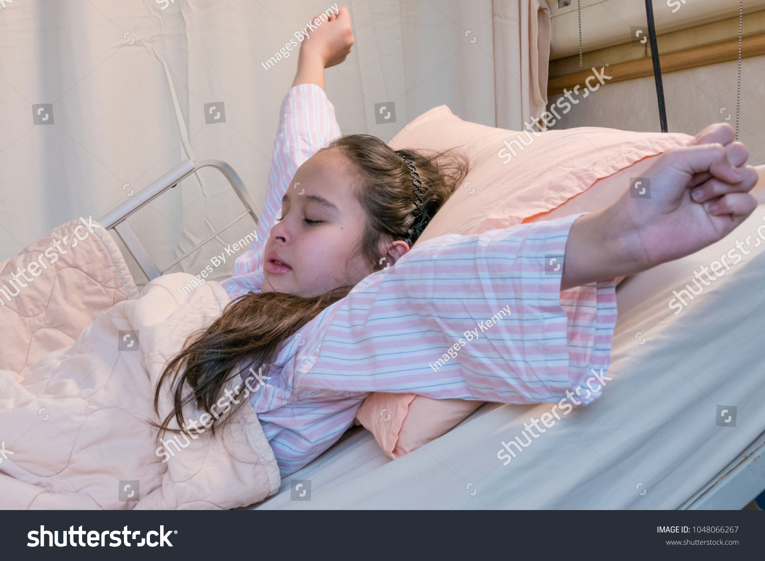 Mixed race Asian American tween girl stretching on hospital bed
